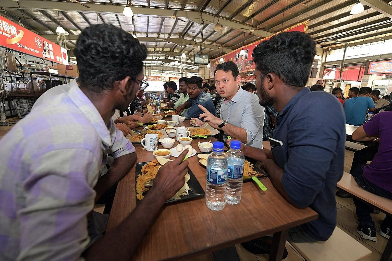 Minister of State for Manpower Zaqy Mohamad sharing a meal yesterday with foreign workers attending the Settling-In Programme at the SCAL Recreation Centre in Soon Lee Road. The one-day orientation course is currently compulsory for all new non-Malay