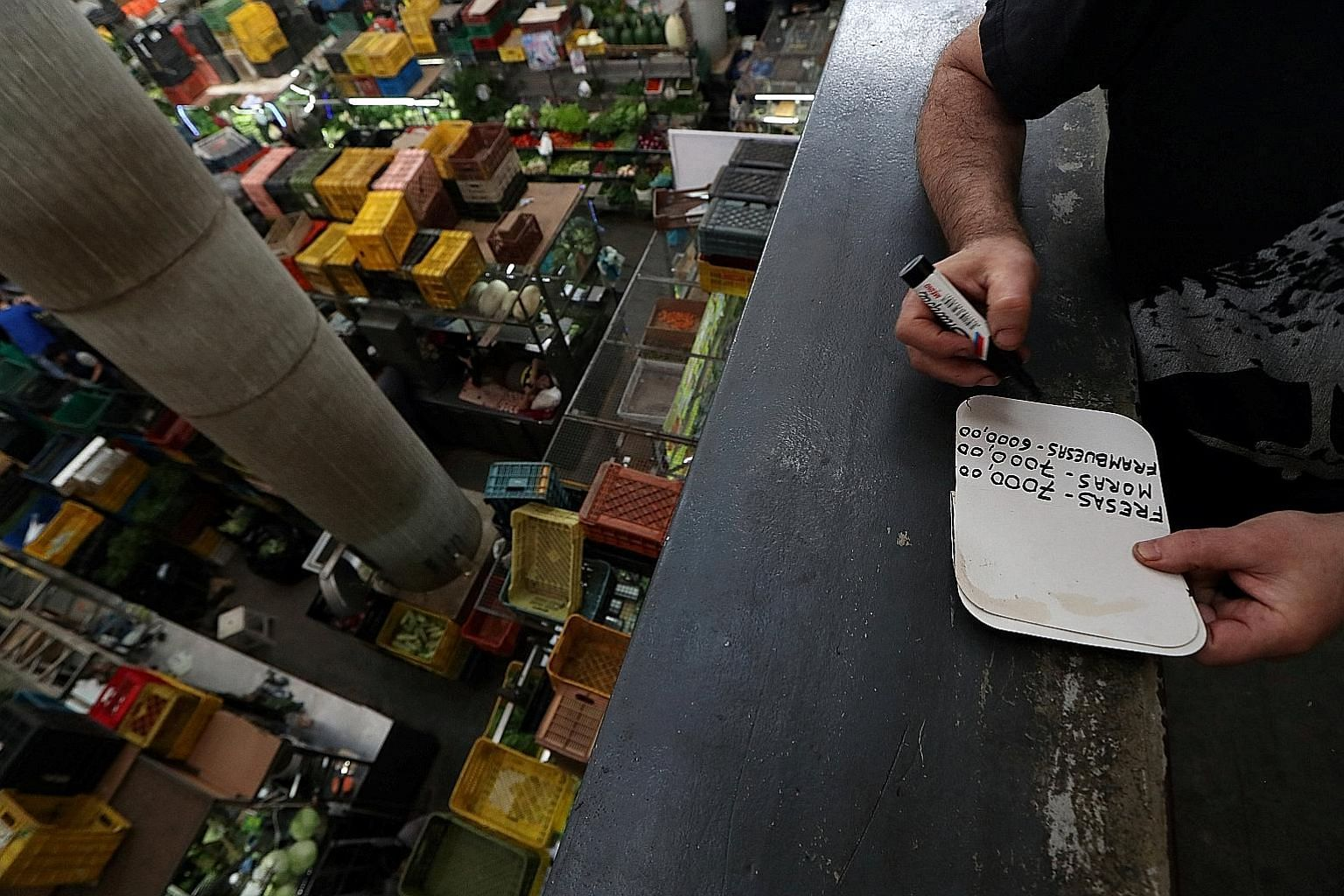 A Venezuelan man making a price list at a commercial centre in the country's capital Caracas last month. Inflation in the beleaguered South American nation is projected to hit an eyeball-popping 8 million per cent this year.
