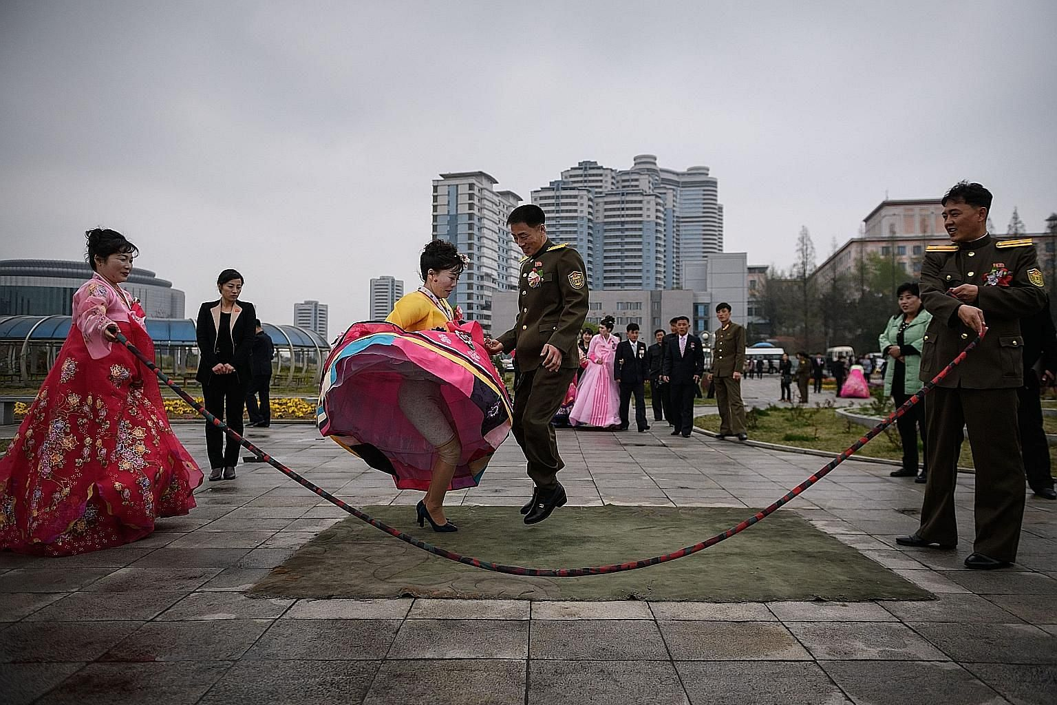 "A bride and groom jumping over a skipping rope as they pose during a wedding photo shoot at a park in North Korea's capital, Pyongyang, on Thursday. With the country's emerging middle class and ""new rich"" business families, lush weddings have become"