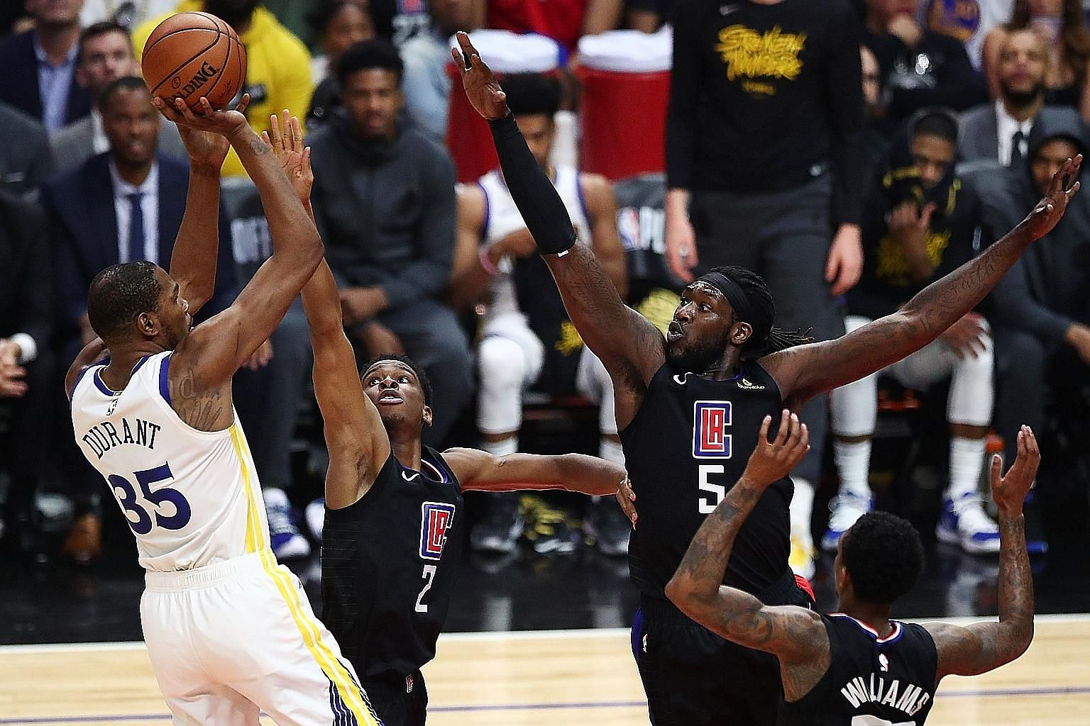 Golden State's Kevin Durant taking a shot despite the attention of the Clippers' (from left) Shai Gilgeous-Alexander, Montrezl Harrell and Lou Williams in Game 3 of their Western Conference first-round play-off series at Staples Centre on Thursday in Los
