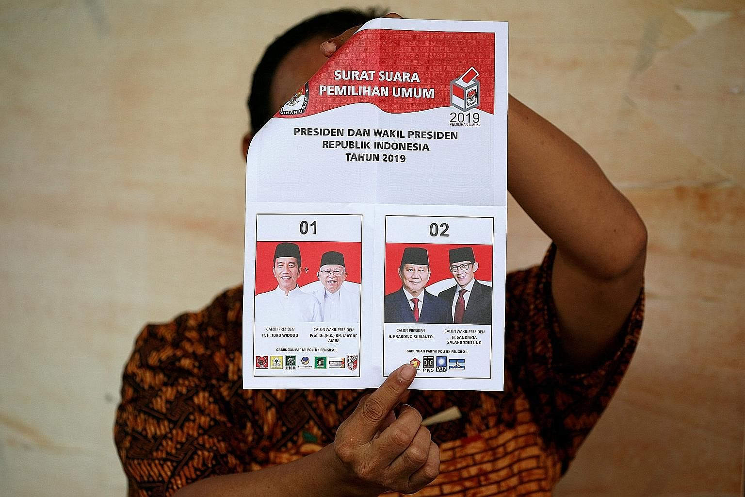 A ballot paper being held up during the tallying of the results for the Indonesian elections in Jakarta on Wednesday. The General Elections Commission predicted that poll turnout would exceed its target of 77.5 per cent. PHOTO: REUTERS