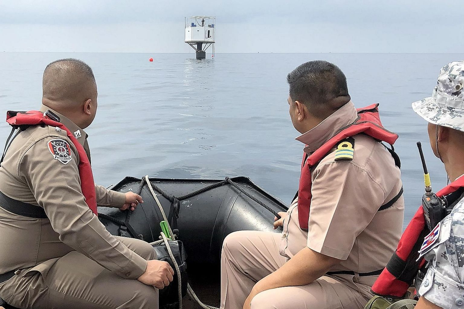 Thailand's Third Naval Area Command officers and Marine policemen observing a floating home in the Andaman Sea, some 12 nautical miles off the coast of Phuket. The couple who built the house may face the death penalty.