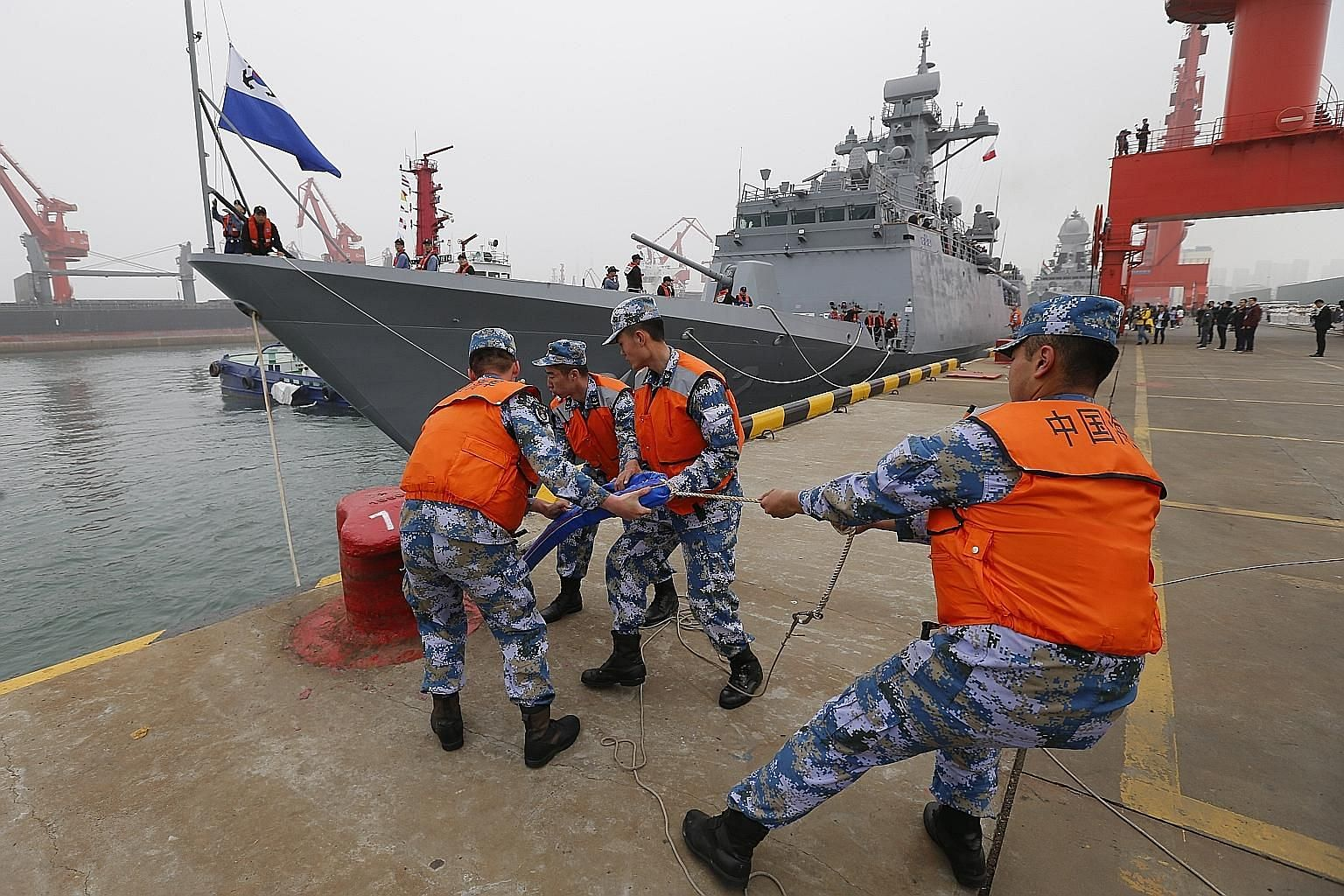 Chinese navy soldiers mooring the Korean Incheon-class frigate ROKS Gyeonggi FFG-812 at a port in Qingdao, China, yesterday. PHOTO: EPA-EFE