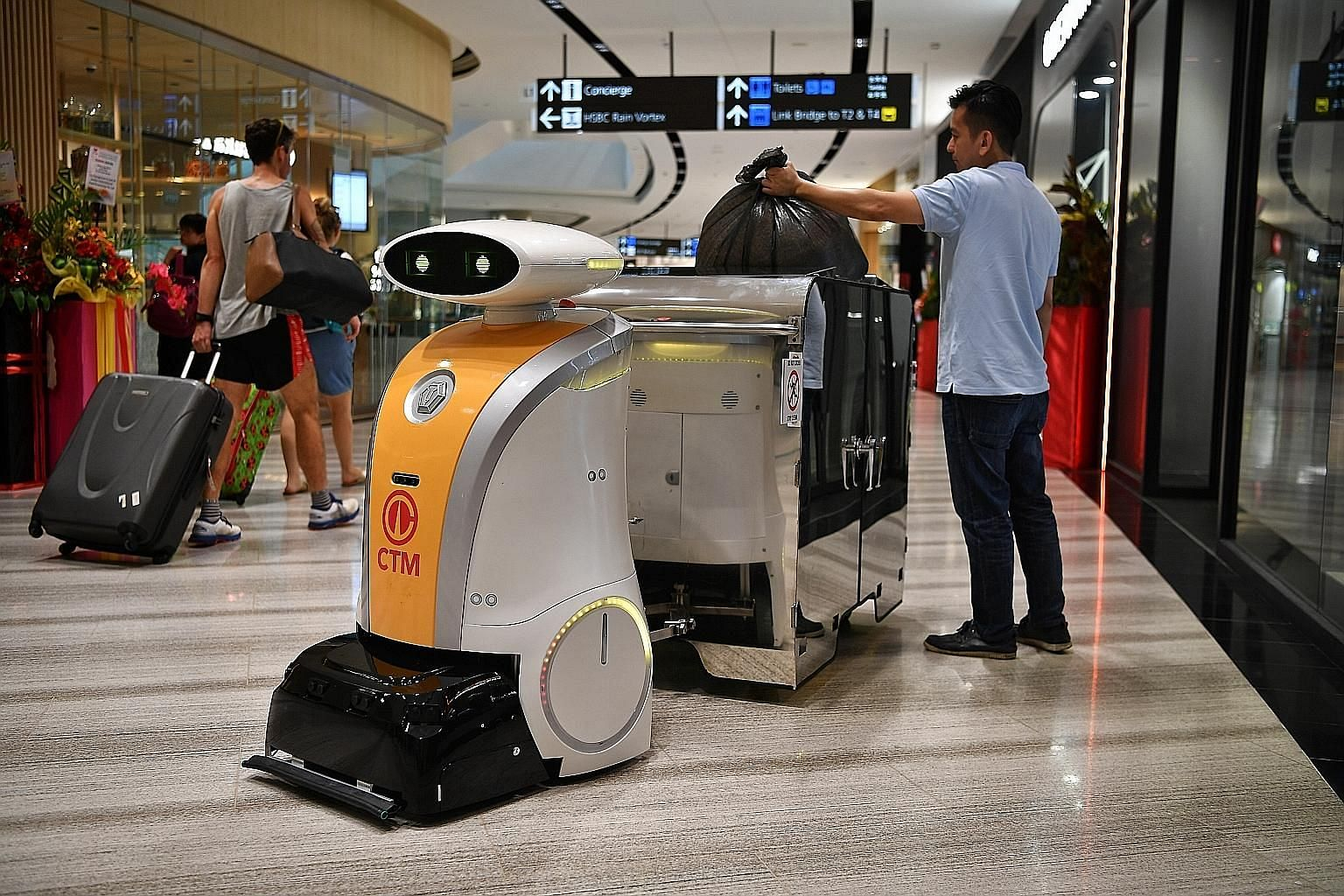 Left: Yi Wei, a robot deployed at Jewel Changi Airport, can pull a 1,000-litre bin along a pre-mapped route. Above: Ella, a scrub robot deployed at the National Gallery Singapore, is fitted with soft brushes for the conserved tiles. ST PHOTOS: CHONG