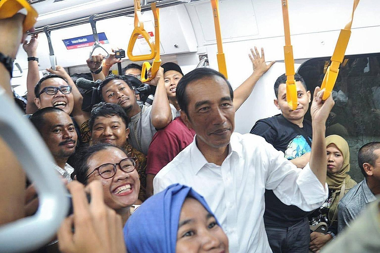 President Joko Widodo surrounded by commuters while taking the new MRT line in Jakarta on Sunday. Quick-count results by local pollsters showed the President as most likely to win the election, a result now being contested by his opponent, Mr Prabowo