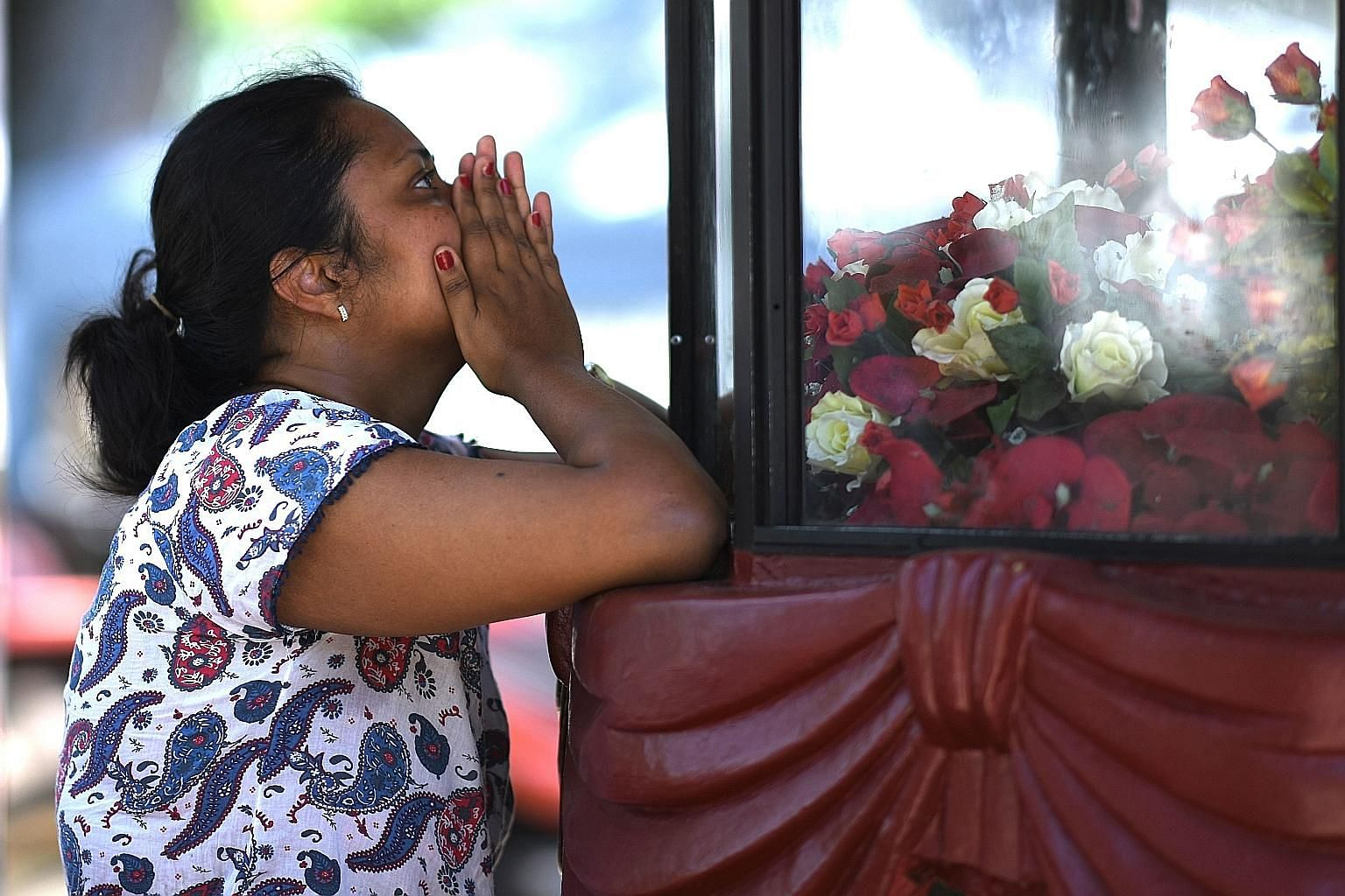 A woman praying yesterday at St Sebastian's Church, which was hit in the bomb blasts on Easter Sunday. Islamic outfit National Thowheeth Jama'ath has been fingered as a possible suspect in the attacks.