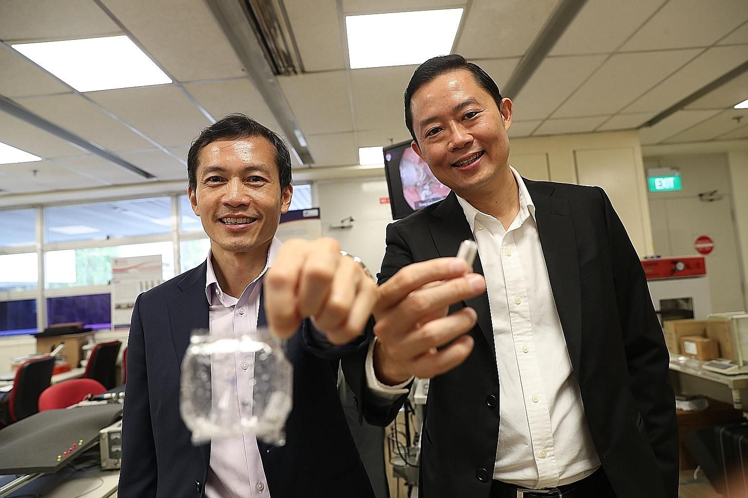 Professor Lawrence Ho (left), clinician-innovator at the National University Health System, with the expanded EndoPil capsule, and Professor Louis Phee, dean of engineering at Nanyang Technological University, with the pre-inflated capsule that is de