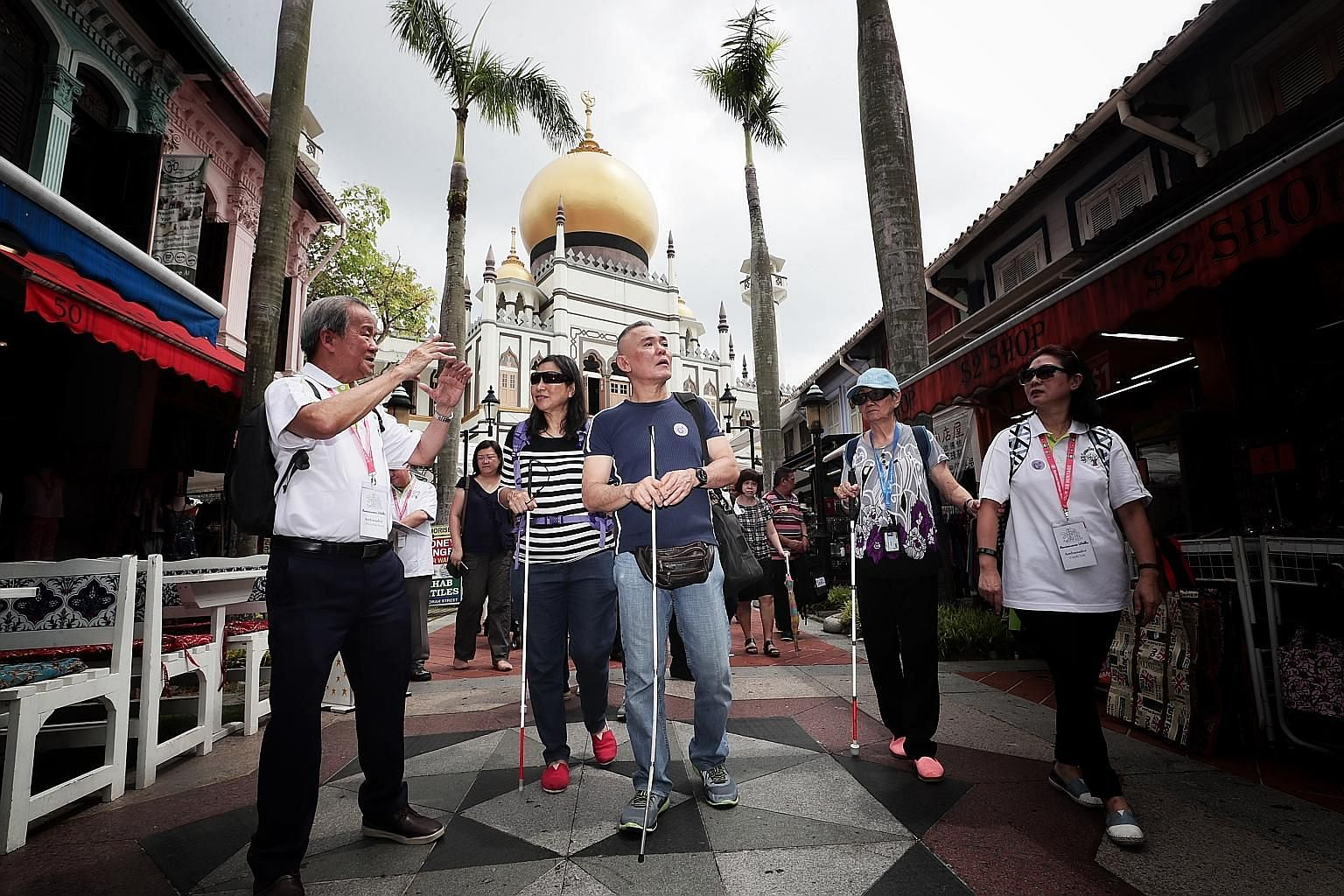 Senior ambassador Chhua Bak Siang (far left) guiding visually impaired participants from Guide Dogs Singapore, including masseur Tan Chiew Song (in blue), around Kampong Glam heritage precinct, as part of the NHB's Reminiscence Walks programme.