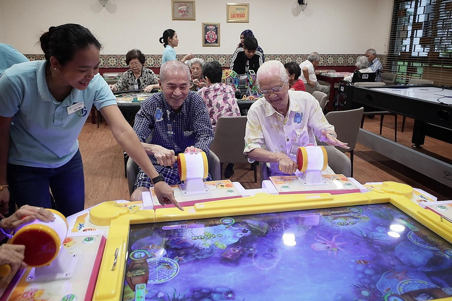Retiree Robin Liow (centre), 72, who has Parkinson's disease and suffered a hip fracture last year, playing an arcade game with fellow retiree Teo Cheng Lok, 85, in the games room at the senior care centre in Ghim Moh. They are guided by Ms Moh Moh,
