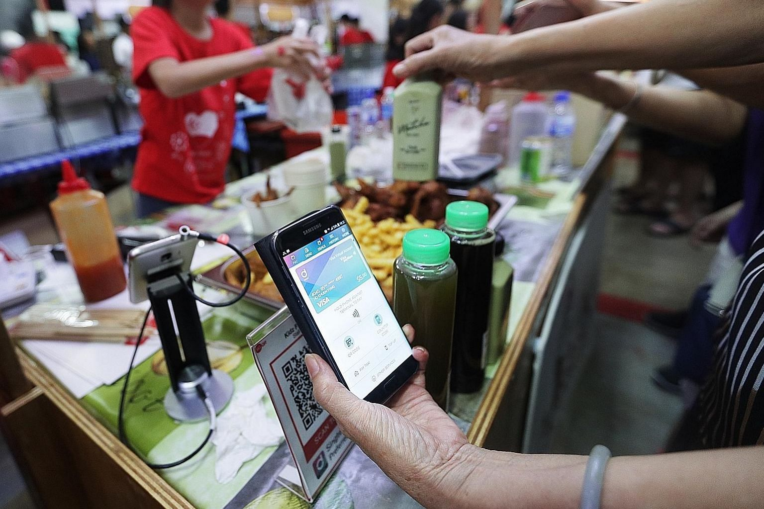 Fraud is a rising concern as more people now use e-wallets (left) on their smartphones. The guidelines contain new measures to better balance risky user behaviour with the potentially large losses that financial institutions are exposed to.
