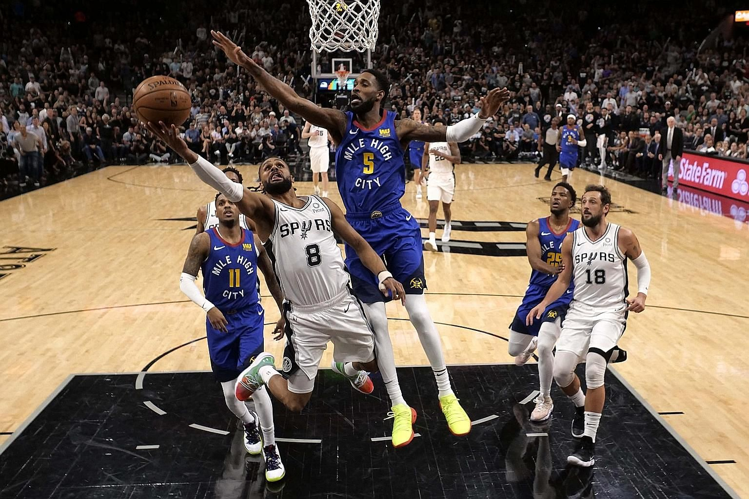 San Antonio's Patty Mills going for the basket while under pressure from Denver Nuggets' Will Barton during Game 6 of their NBA play-off first-round series. Spurs won 120-103.