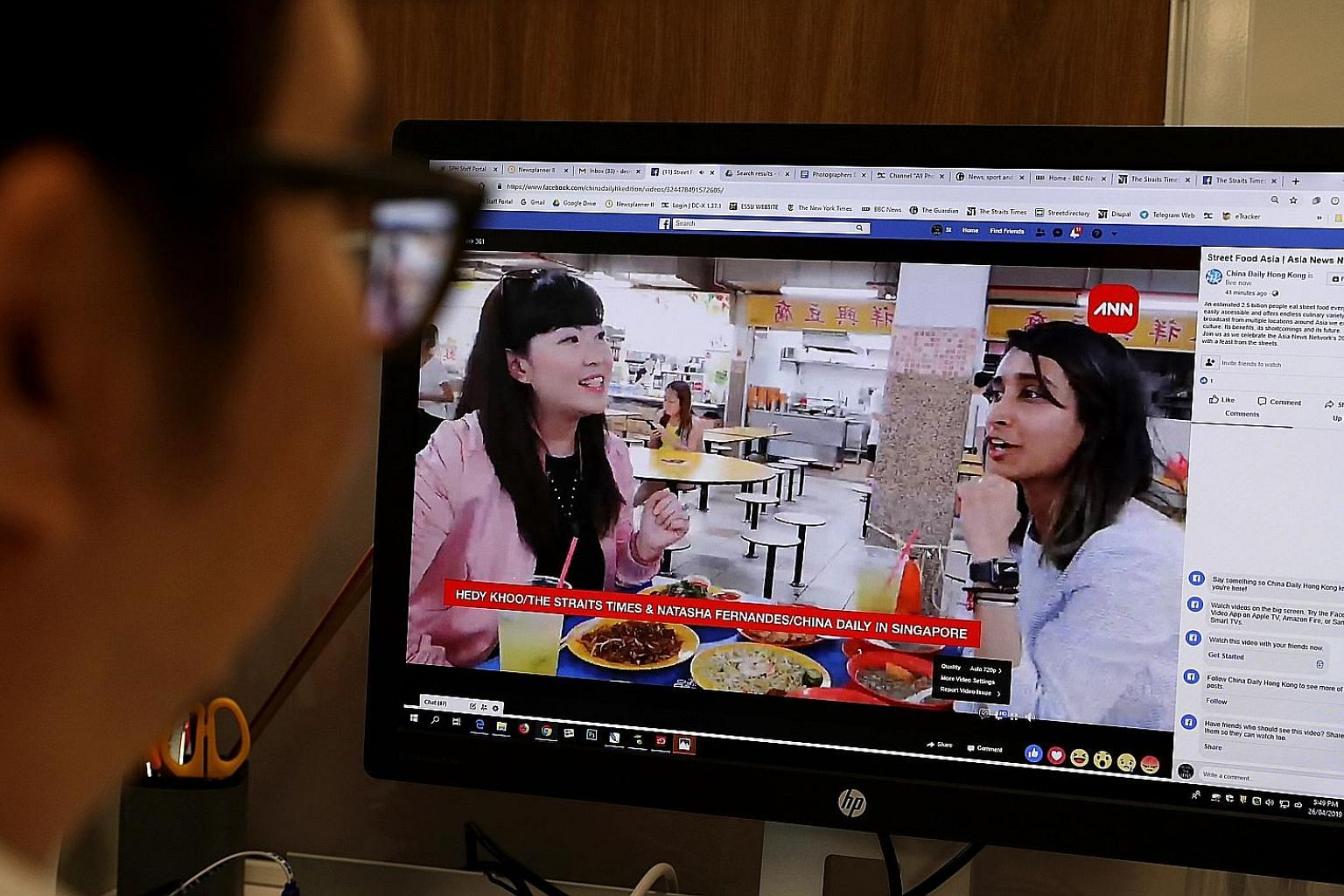 A viewer watching The Straits Times' STFood online editor Hedy Khoo (left) and Hong Kong's China Daily senior multimedia producer Natasha Fernandes' Facebook livestream yesterday from People's Park Centre in Singapore, where they tucked into local st