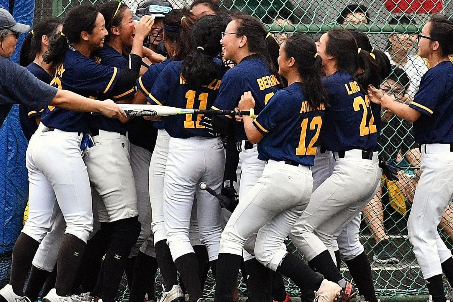 Anglo-Chinese Junior College players mobbing Shino Lim after her home run in the 5-0 win over Hwa Chong Institution on Monday in the Schools National girls' A Division softball final. The match at Raffles Institution was completed yesterday after bad