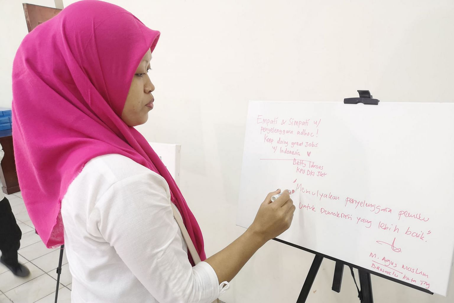 Madam Masnun, the widow of a security officer who died of exhaustion and heart pain after working long hours at a Bekasi polling station, writing a tribute to her late husband and others who succumbed to election fatigue monitoring Indonesia's April