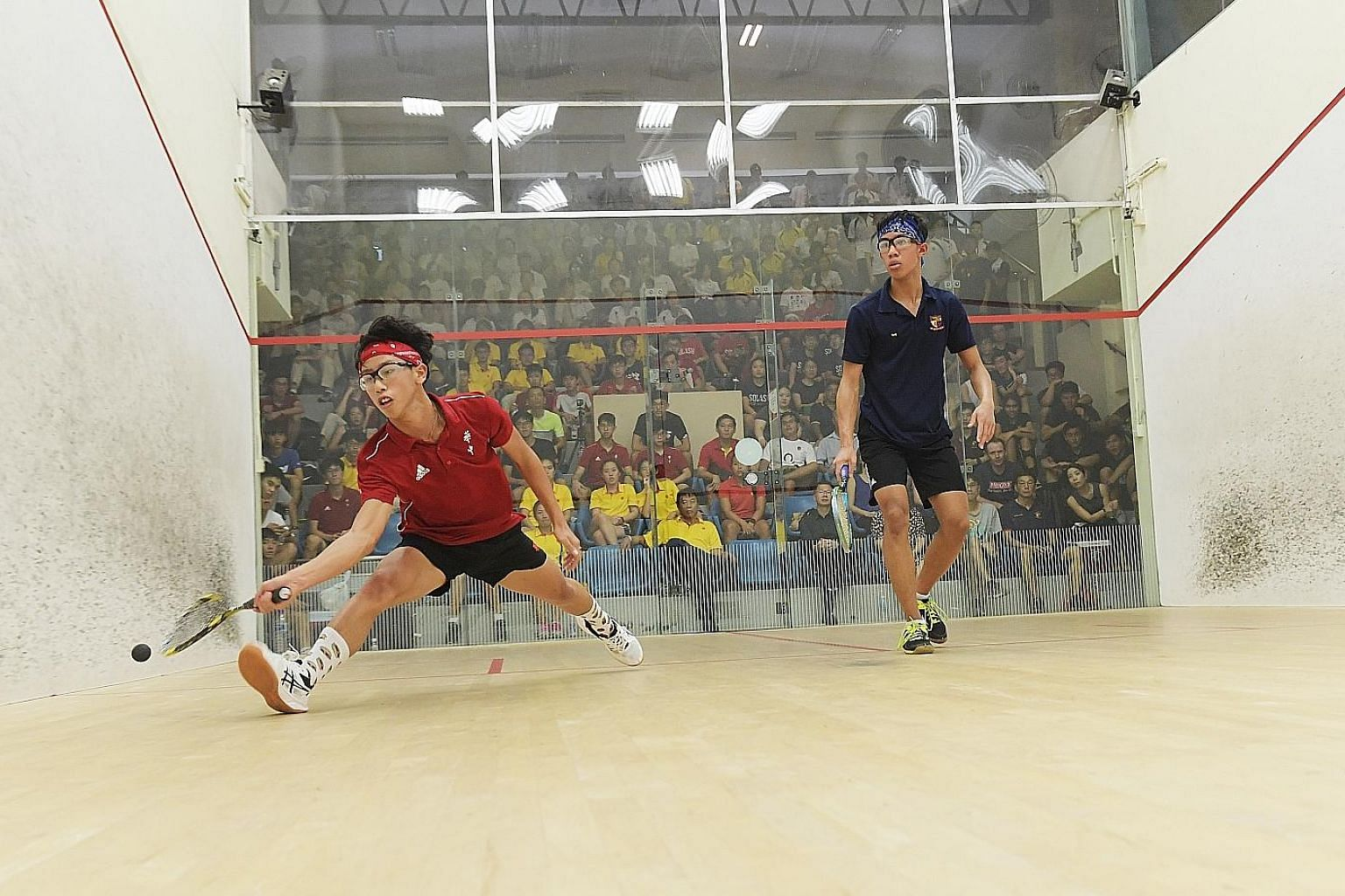 Hwa Chong Institution's Jovan Lee (in red) playing against Rudy Johari of Anglo-Chinese School (Independent) in the third match of the Schools National boys' A Division squash team final at Kallang Squash Centre yesterday.