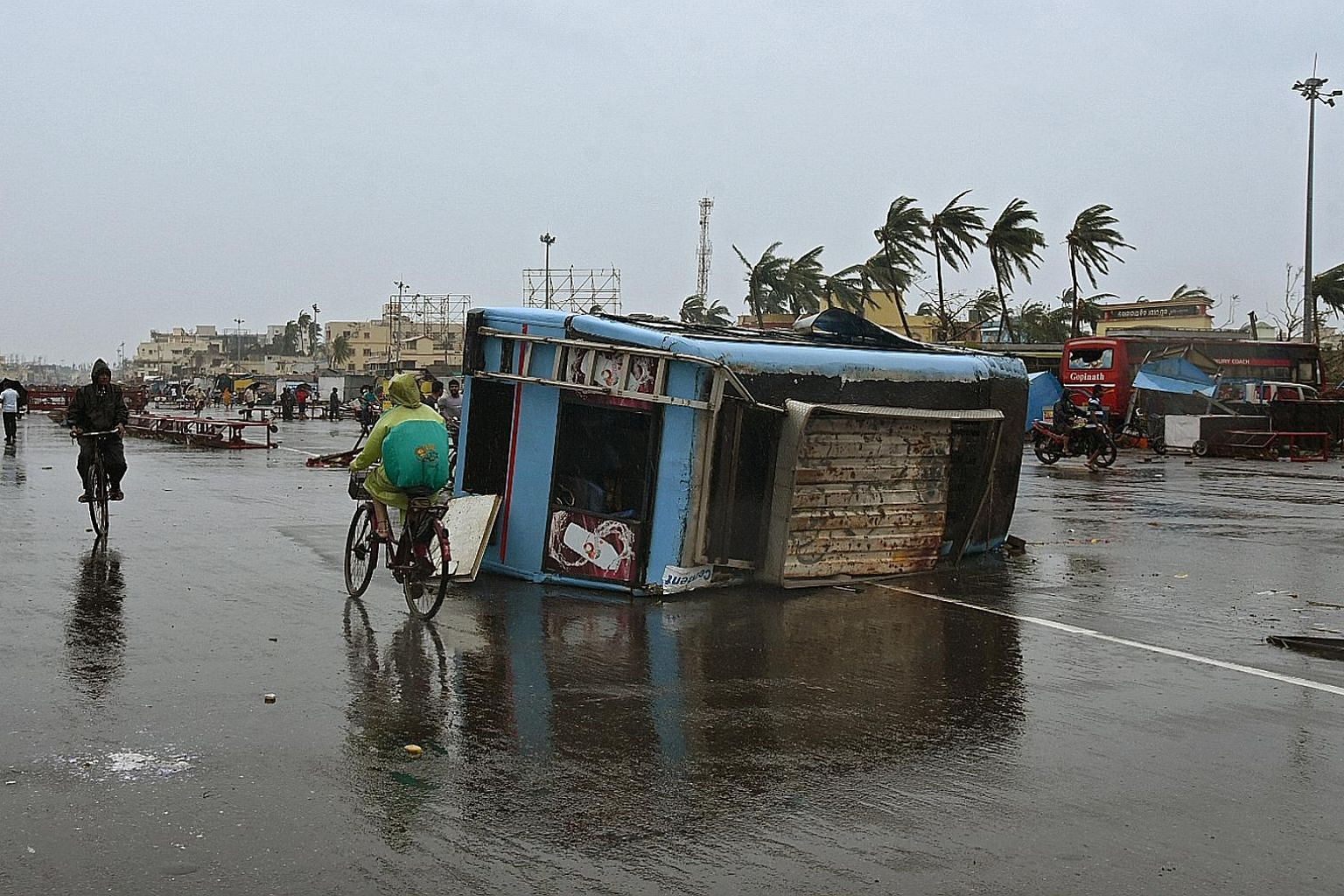 A temporary cyclone relief shelter in Puri, Odisha, yesterday. Around a million people in eastern India have been evacuated ahead of a cyclone with winds of up to 200kmh and torrential rain, officials said. A vehicle damaged after Cyclone Fani hit Pu