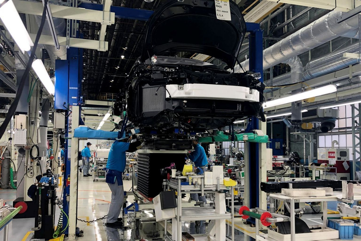 Hydrogen cars boast some of the advantages of batteryelectric cars, including powerful acceleration, silent operation and no emissions at the point of use except water vapour. (Above) Workers install the fuel-cell power system in a Toyota Mirai at a facto