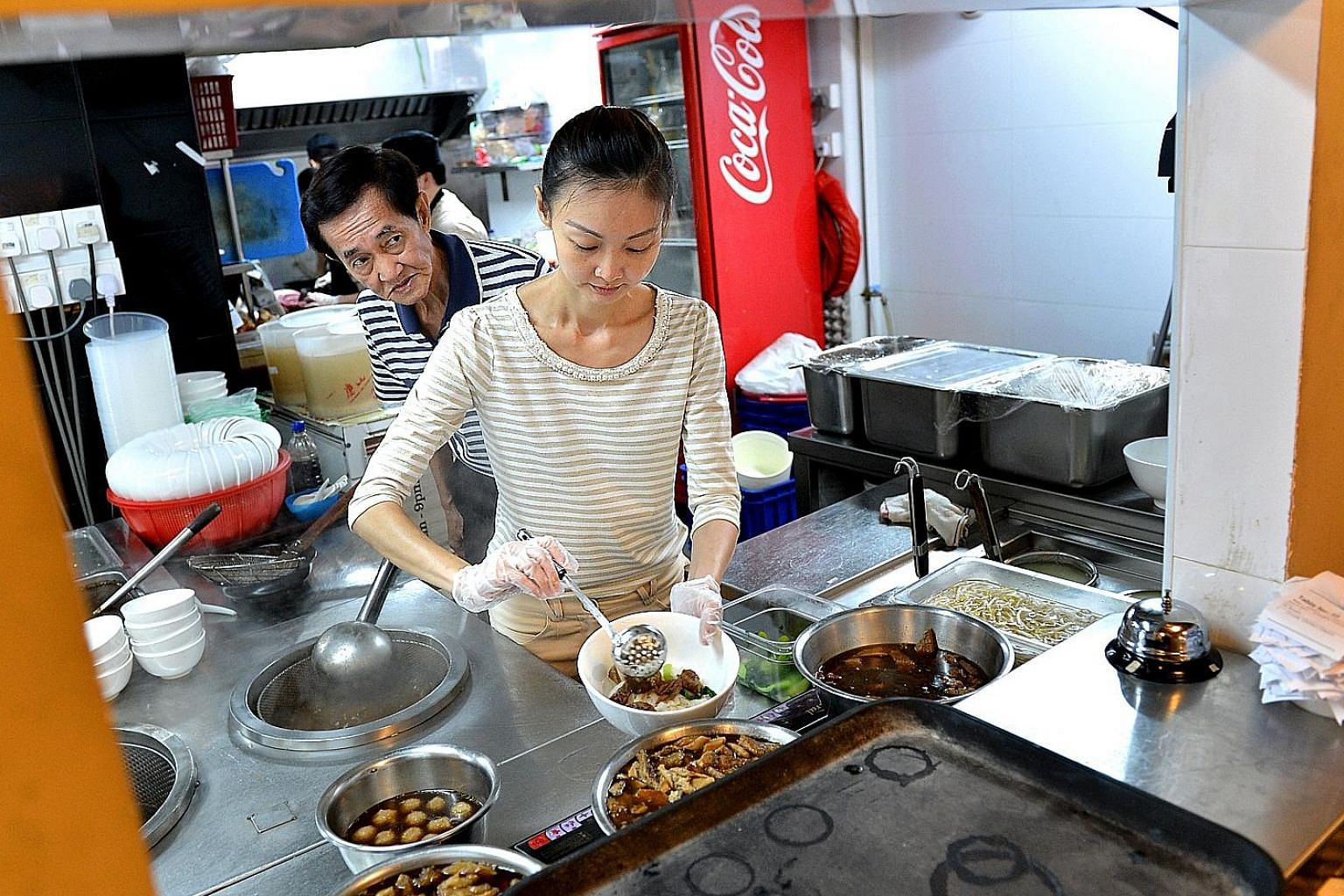 Ms Tina Tan, seen here with her father Anthony, preparing a bowl of beef kway teow.