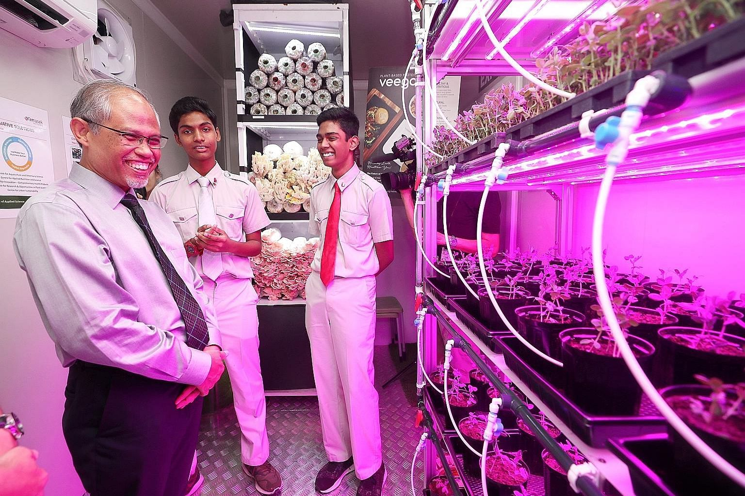 Minister for the Environment and Water Resources Masagos Zulkifli touring the facility with National Junior College students Ahsan Husain Ariff Muhammed (centre) and Shahul Hameed yesterday.