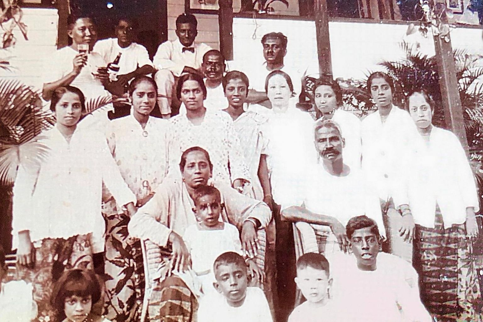 The writer's great-grandaunt Nayagi Packrisamy (seated) with her husband Thiagarajan Packrisamy. This photo, taken some time in the early 1900s at the family's summer house near the beach, includes friends, neighbours and family members, such as the