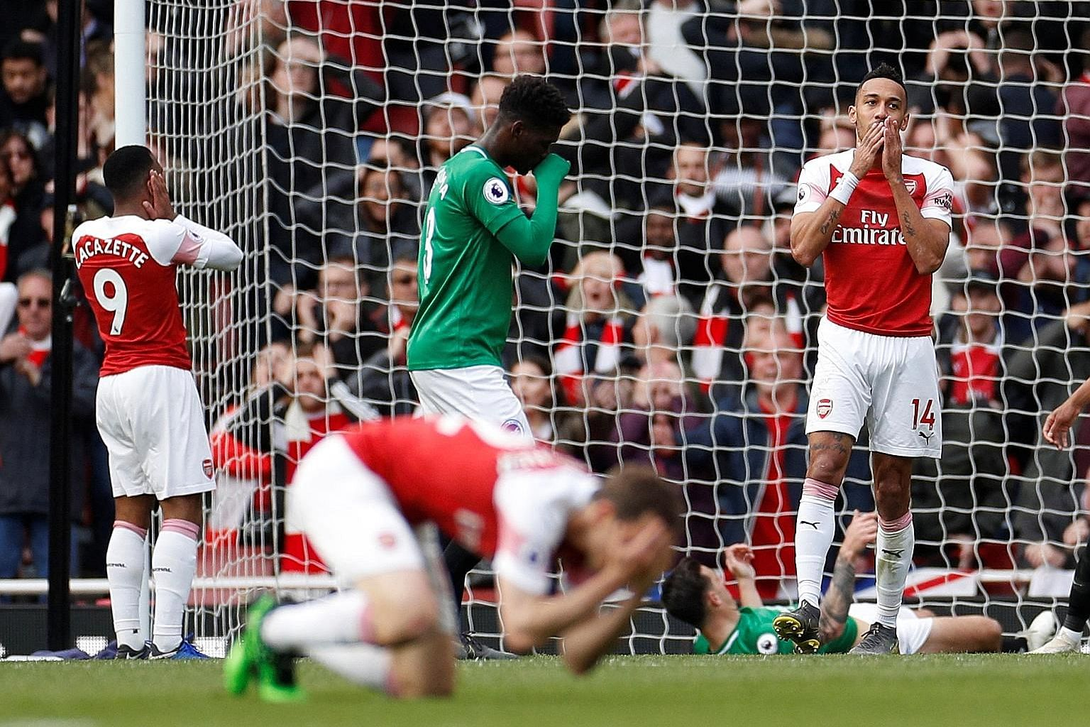 Arsenal's Pierre-Emerick Aubameyang (right) and teammates in disbelief after his miss during the Premier League game against Brighton at the Emirates on Sunday. The teams drew 1-1. PHOTO: REUTERS