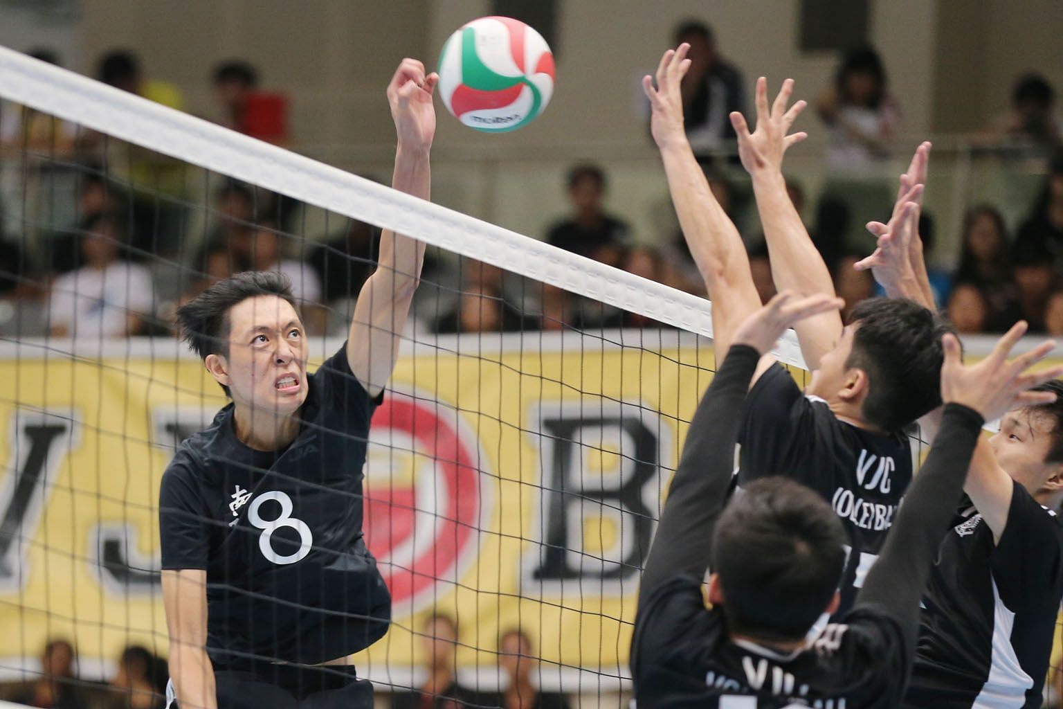 Nicolas Law (left) helping Nanyang Junior College to a 3-1 win over Victoria Junior College in the Schools National A Division boys' volleyball final at Our Tampines Hub yesterday.