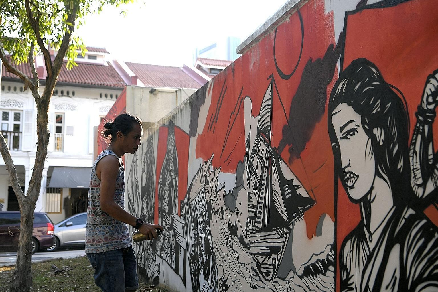 Artist Zul Othman shown here painting the wall surrounding Gedung Kuning, a historical royal building in Kampong Glam. Mr Zul's mural tells the tale of Wak Cantuk, who went on a killing spree in the 1800s after his marriage proposal was rejected. Som