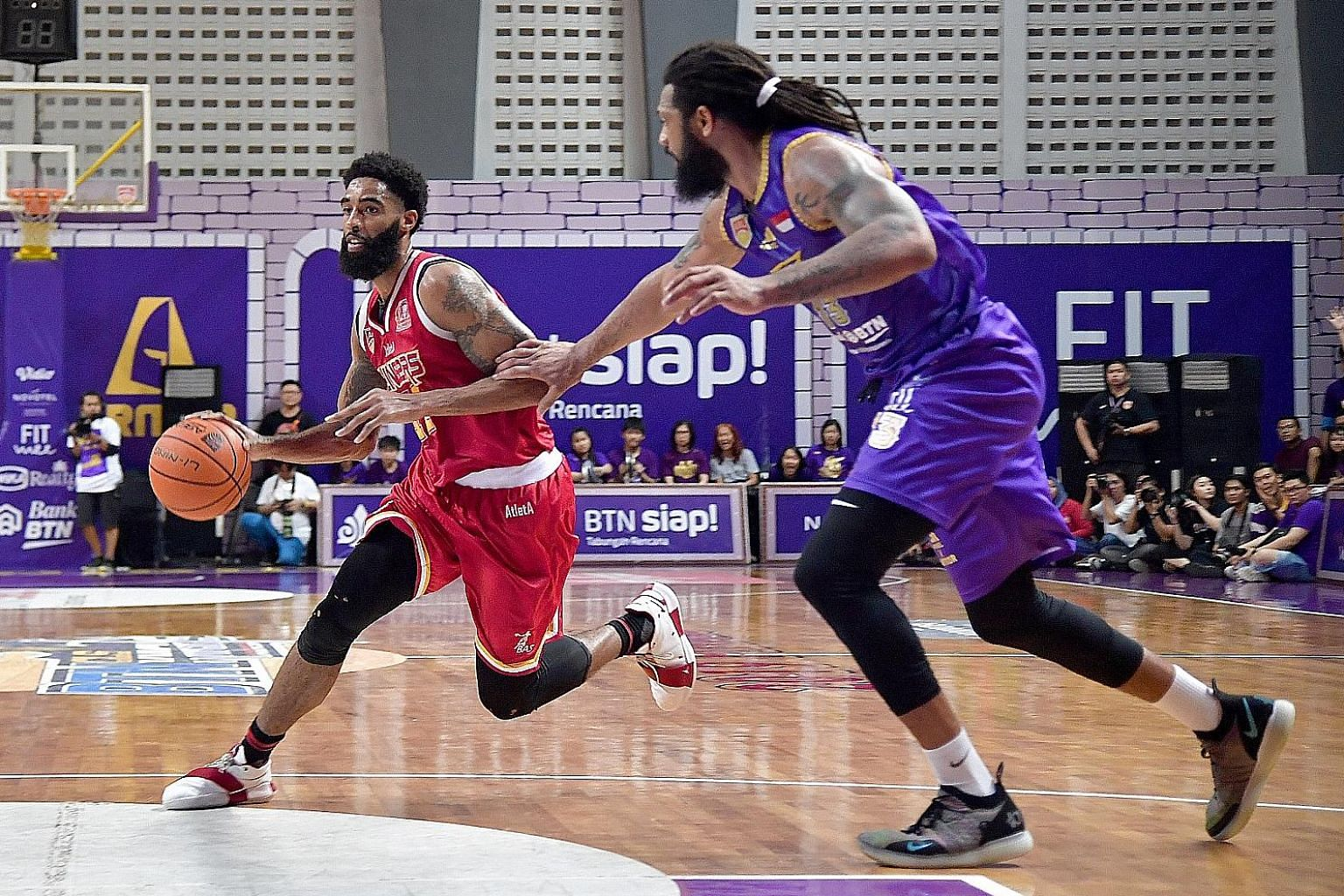 Singapore Slingers' Jerran Young being guarded by CLS Knights Indonesia's Darryl Watkins in Game 3 of the Asean Basketball League Finals in Surabaya on Wednesday. He has overcome a hamstring injury in their Game 1 loss to help the team come back with