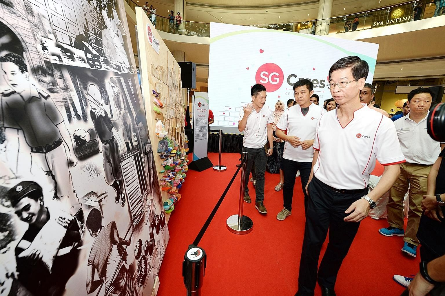 Dr Ang Hak Seng, Deputy Secretary of the Ministry of Culture, Community and Youth (foreground), and Speaker of Parliament Tan Chuan-Jin (middle) viewing a mural project at Suntec City yesterday.