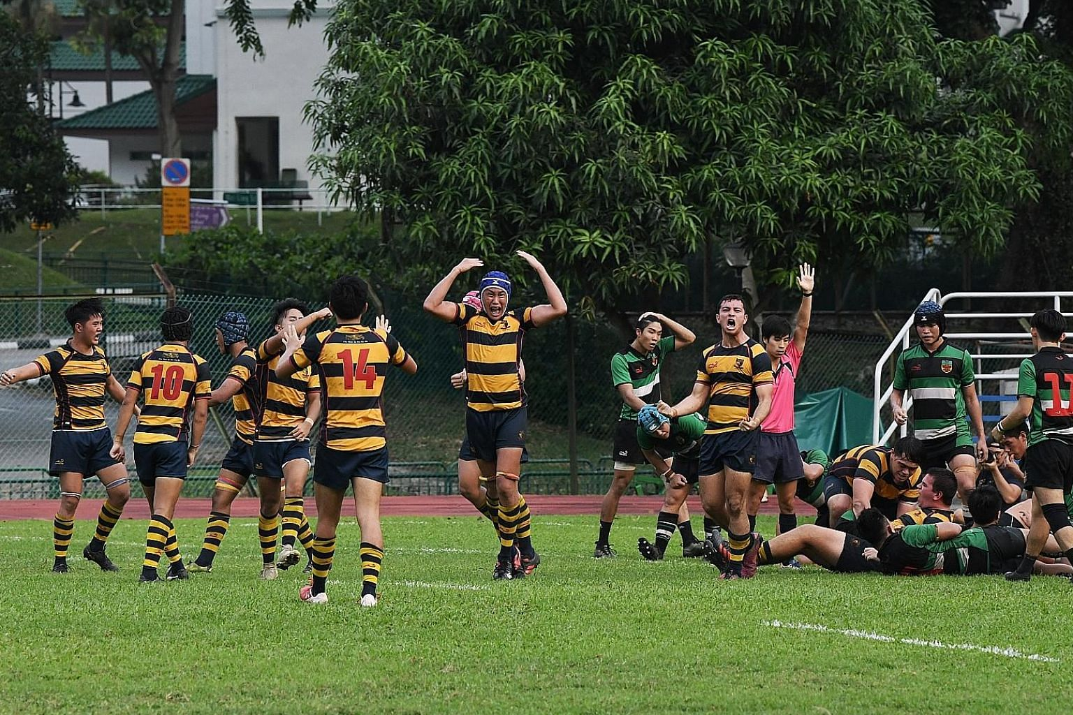 ACS(I) players cheering after the team scored their second try to regain the lead - this time for good. ST PHOTO: KHALID BABA