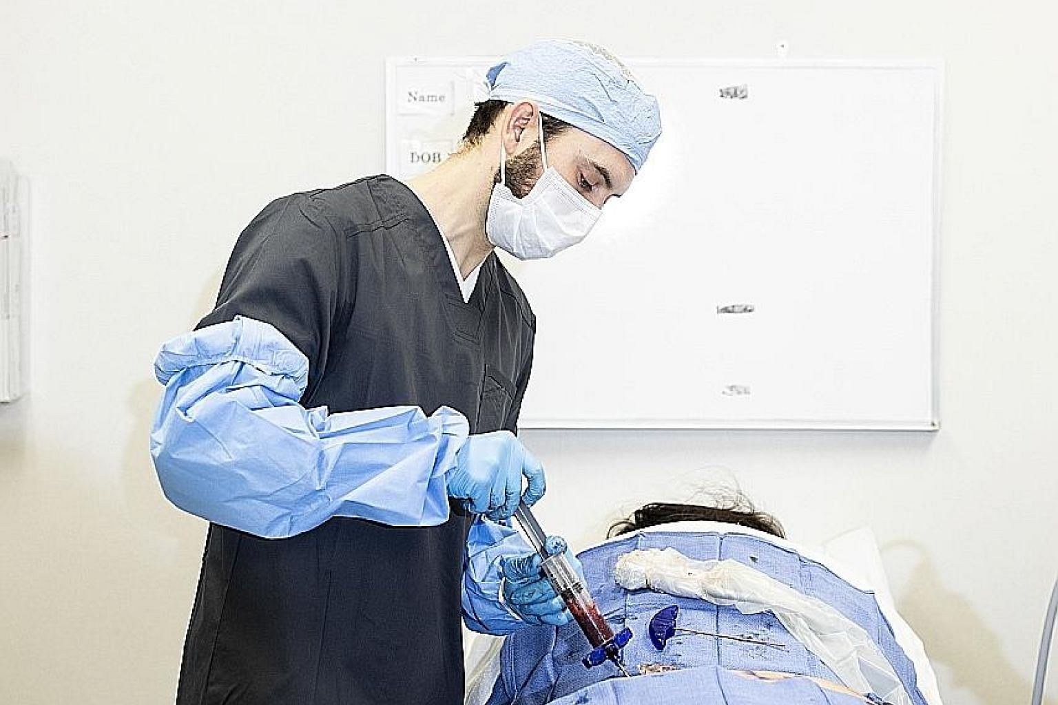 A doctor extracting bone marrow from a patient's pelvic bone at a clinic in the US for a stem cell procedure earlier this year. The Food and Drug Administration has taken an industry-friendly approach towards companies using unproven cell cocktails t