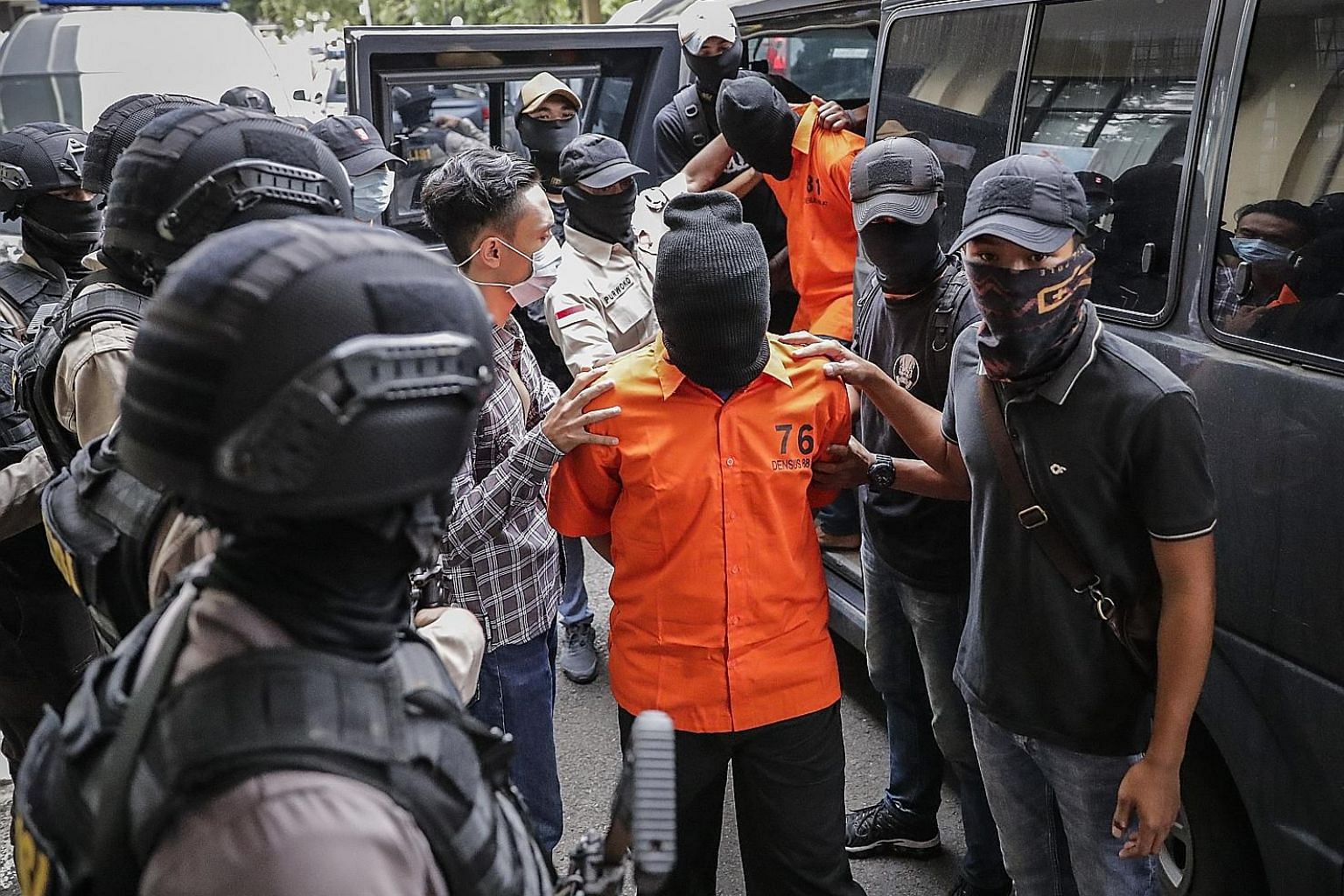 Suspects being escorted by anti-terror police officers before a press conference at the police headquarters in Jakarta yesterday. Six of the nine men nabbed had travelled to join ISIS in Syria.