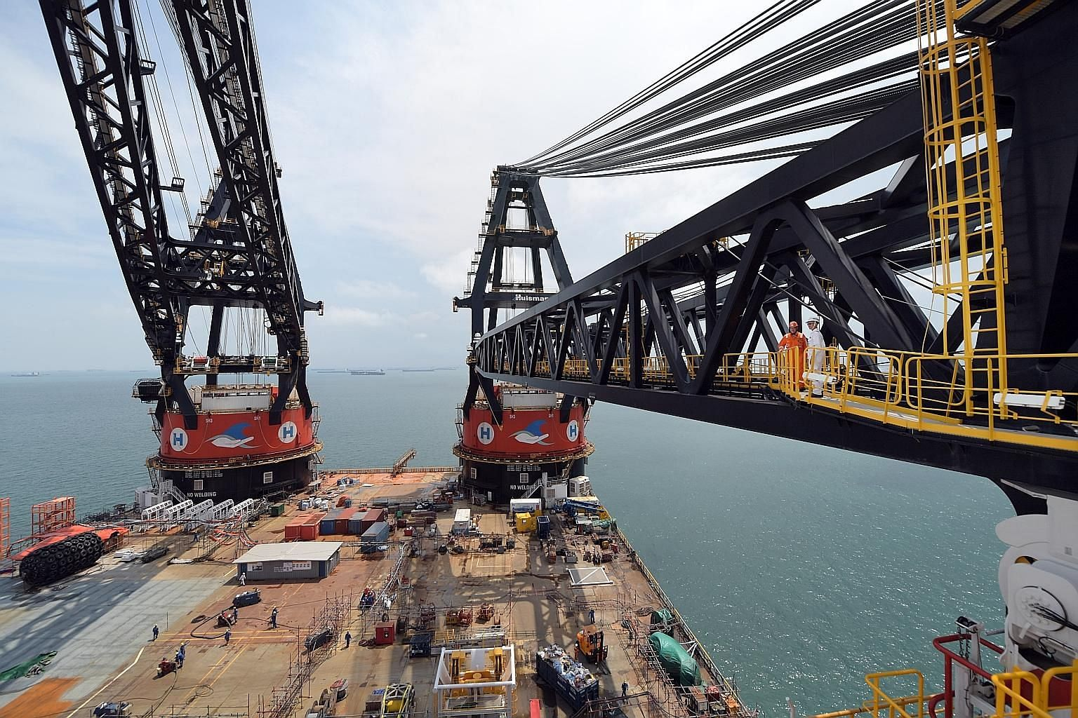Workers are dwarfed by the Sleipnir's eight column legs, each 23.75m tall. The legs conceal the ballast tanks, which take in or release sea water to adjust the vessel's draft (the vertical distance between the waterline and the bottom of the hull), a