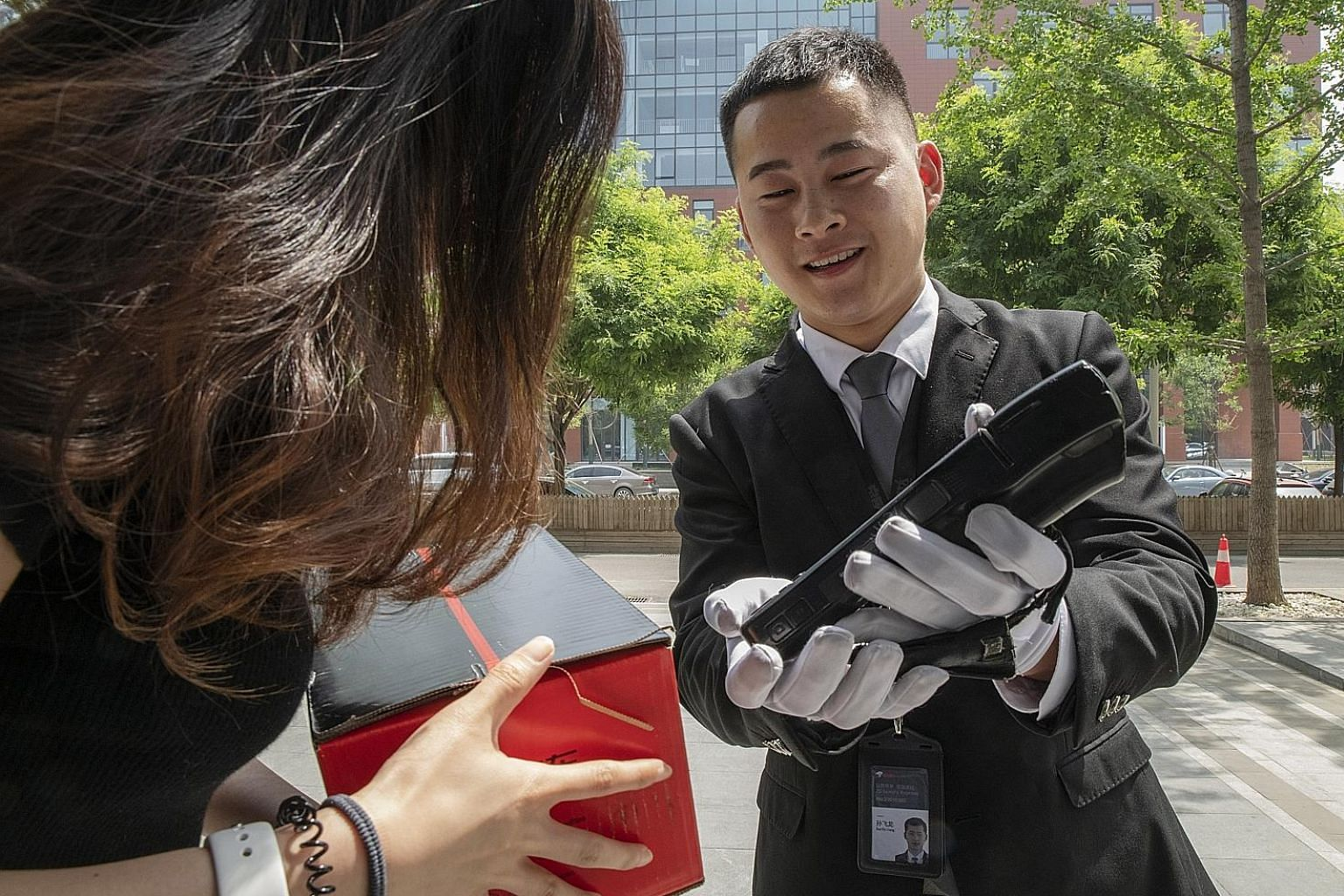 A driver for JD.com's Luxury Express delivery service getting a customer in Beijing to acknowledge receipt on a handheld device. Big names in luxury are teaming up with Internet companies to offer sales and services, like JD.com's white-gloved butler