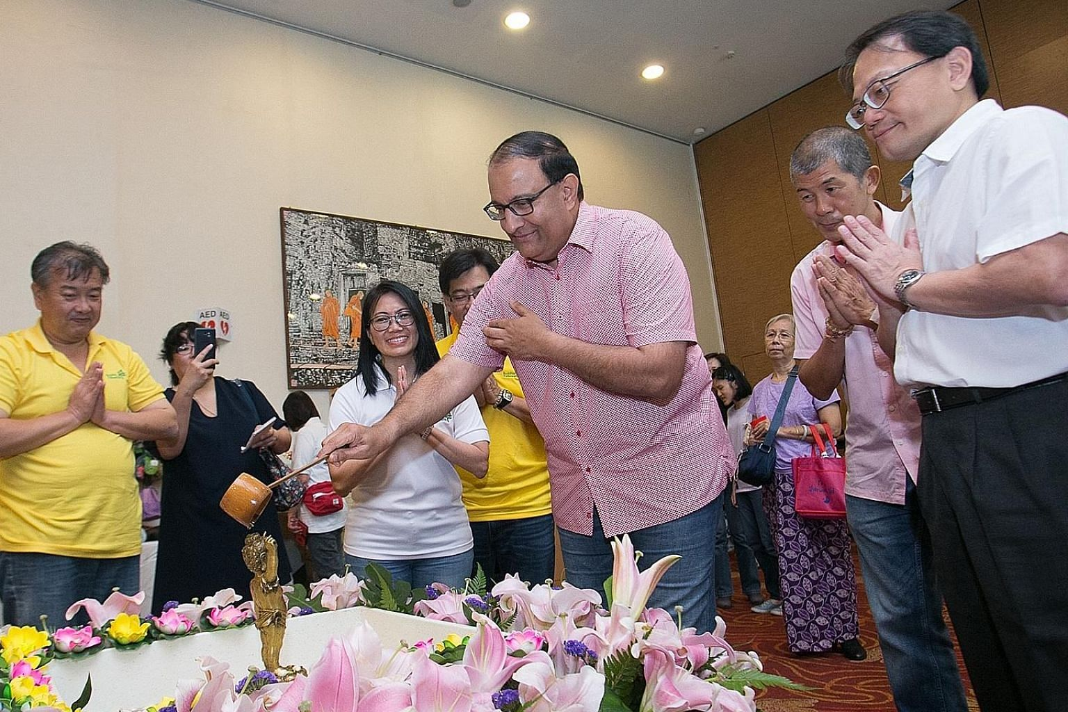 Minister for Communications and Information S. Iswaran bathing a statue of Siddhartha Gautama yesterday at the Vesak Day celebrations. With him are Buddhist Fellowship president Lim Phang Hong (far right) and deputy president Jerry Ong (second from r