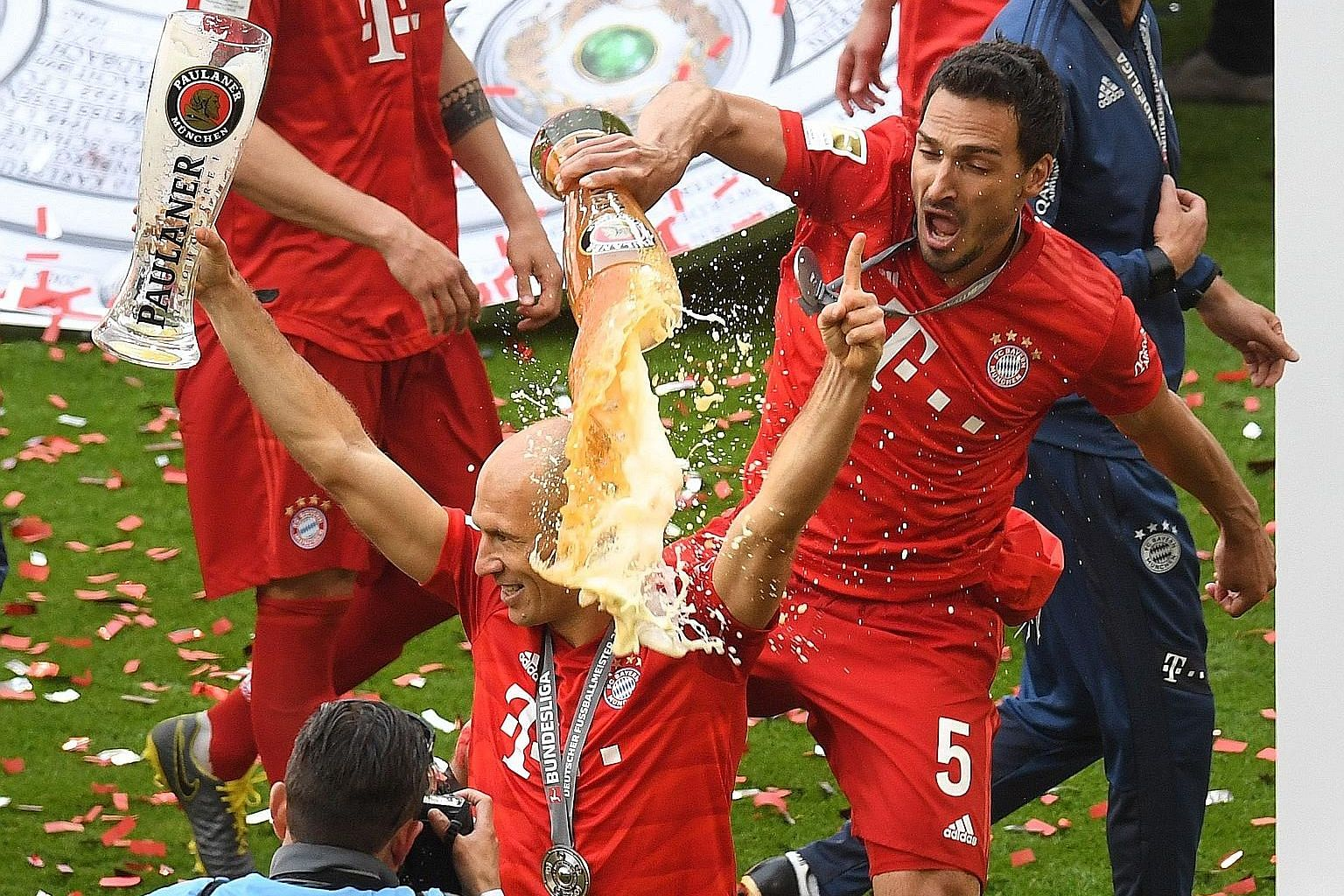 Bayern defender Mats Hummels pouring beer over departing veteran midfielder Arjen Robben after the team thumped Frankfurt at home to win the title on Saturday. PHOTO: AGENCE FRANCE-PRESSE