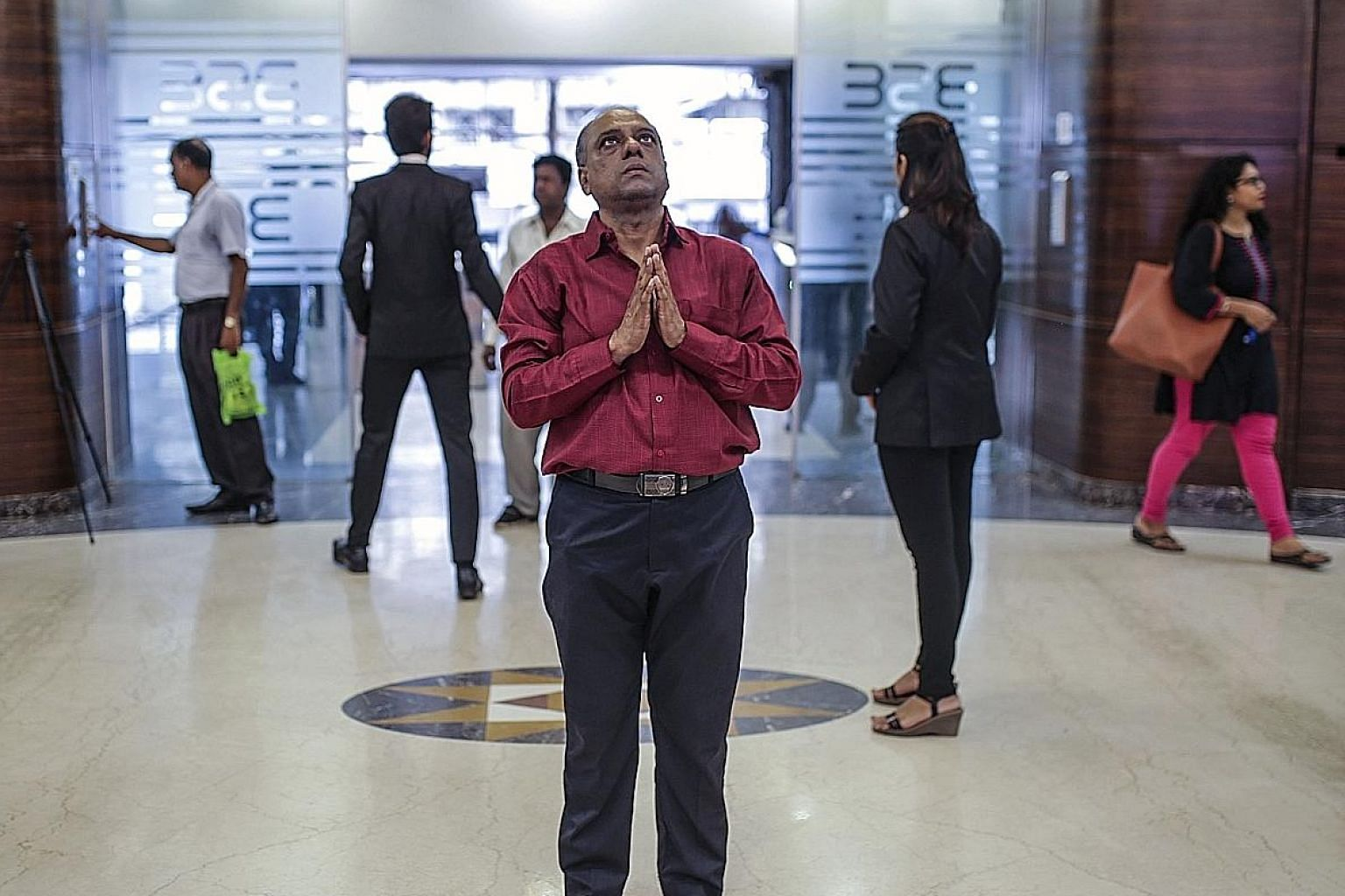 A man praying to a deity on display at the Bombay Stock Exchange building in Mumbai. The exchange's Sensex index had its biggest one-day gain in nearly six years to close at a record high, while the rupee strengthened against the US dollar.