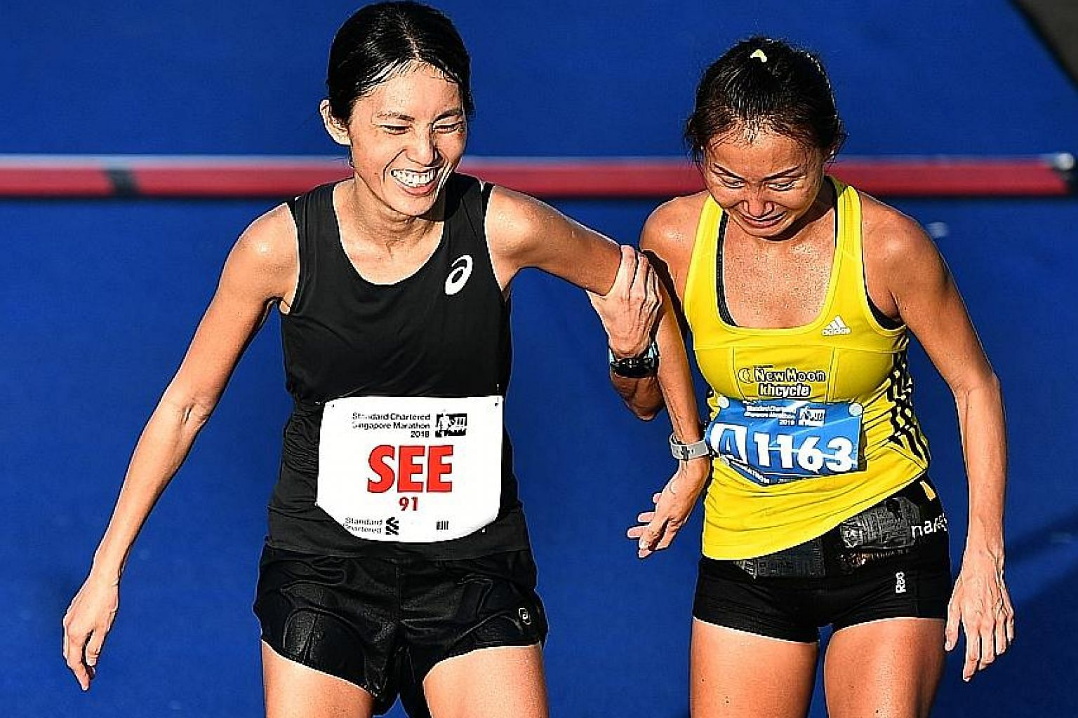 Lim Baoying helping Rachel See after the latter crossed the finish line at the Standard Chartered Singapore Marathon on Dec 9 last year. The change in standings means See retained her 2017 title.
