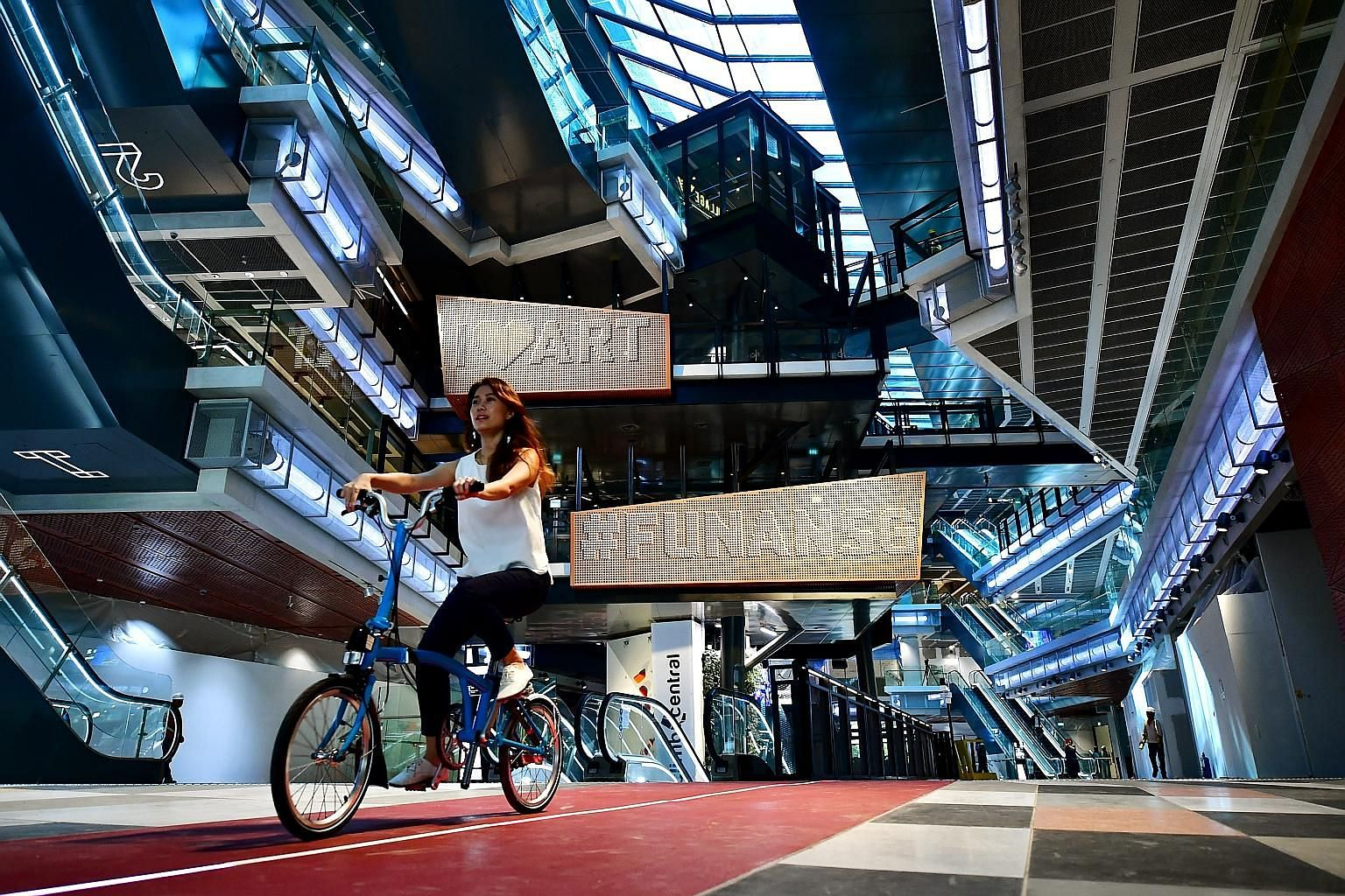 Ms Fionna Lee (above right), 26, a senior executive at CapitaLand, cycling on the path in the new Funan mall, which opens next month.