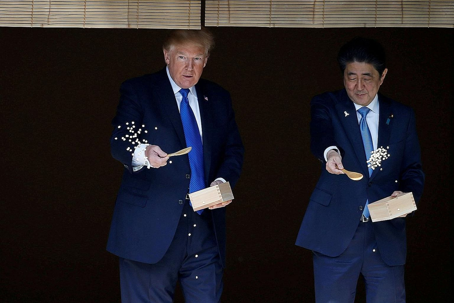US President Donald Trump and Japanese Prime Minister Shinzo Abe feeding carp before their working lunch at Akasaka Palace in Tokyo last November. The Japanese government is taking unprecedented steps to wow Mr Trump upon his arrival in Tokyo on Satu