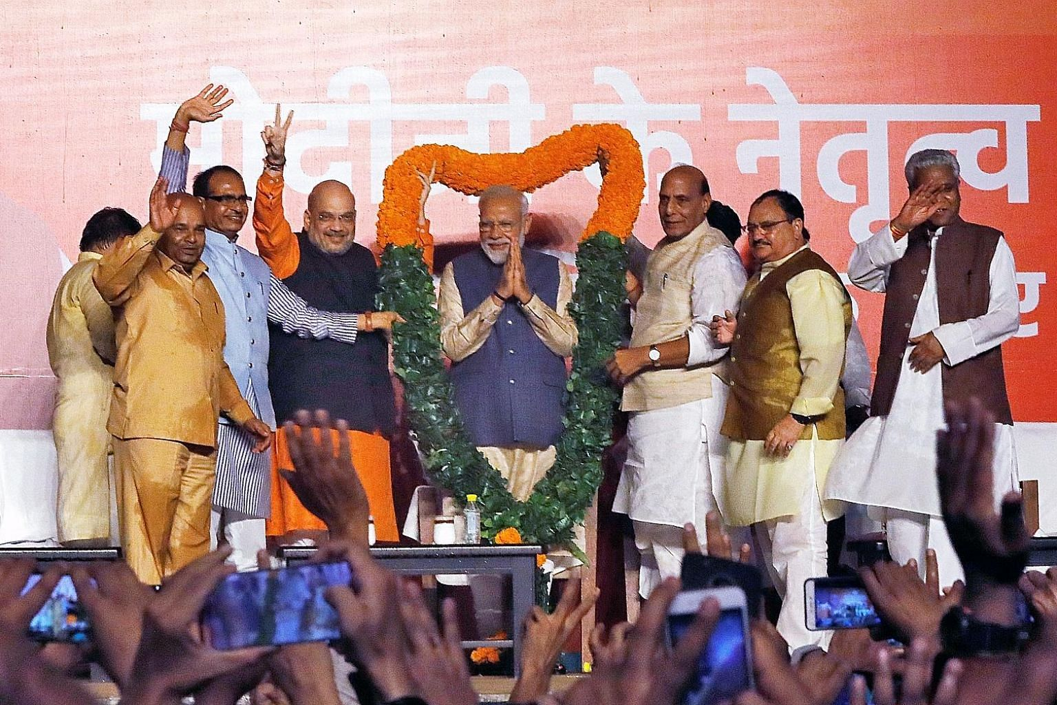 Indian Prime Minister Narendra Modi (centre) being presented with a garland by Bharatiya Janata Party leaders in New Delhi yesterday. By late yesterday evening, Mr Modi's BJP-led alliance was ahead in 351 out of 542 seats. He is only the third prime