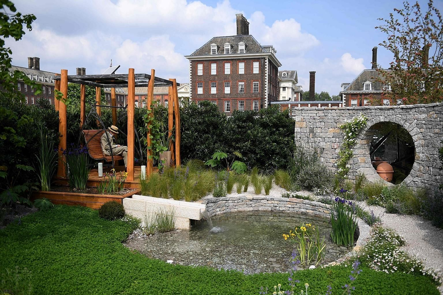 Potted bonsai are among the different plants on display. The Harmonious Garden of Life (above), designed by Laurelie de la Salle, aims to provide a calming experience for visitors. A floral headdress on show. Prince George and Princess Charlotte (bot