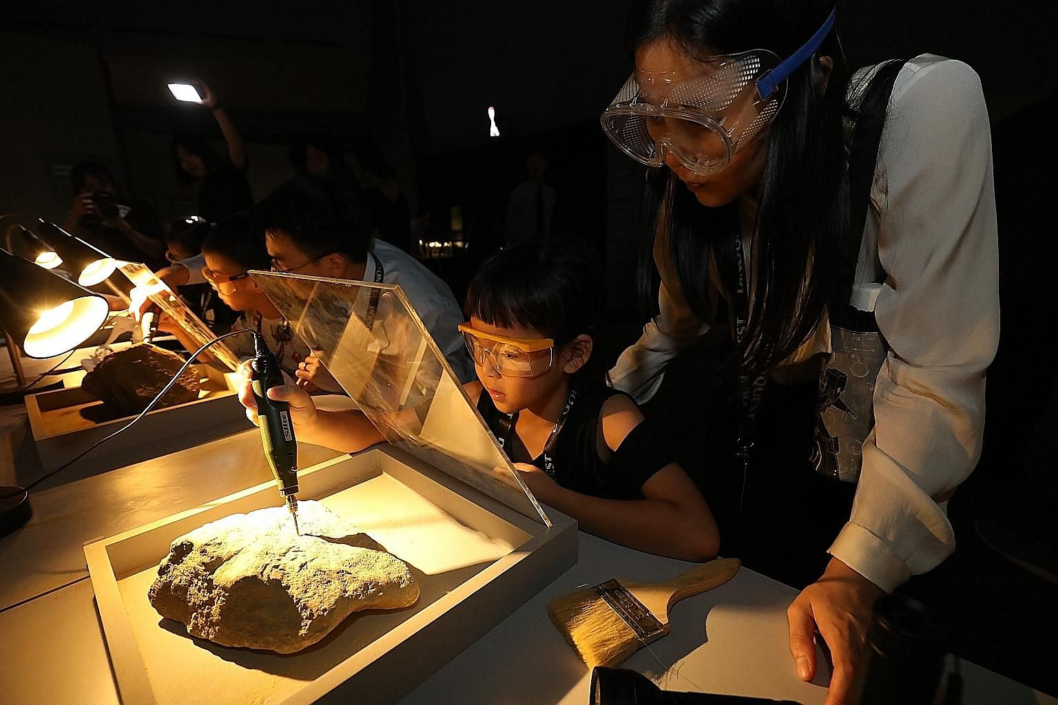 Visitors drilling into rocks to uncover fossils in a hands-on activity at the DinoQuest exhibition in Science Centre Singapore yesterday. The exhibition, which uses digital technology such as holograms, will be open to the public from next Saturday t