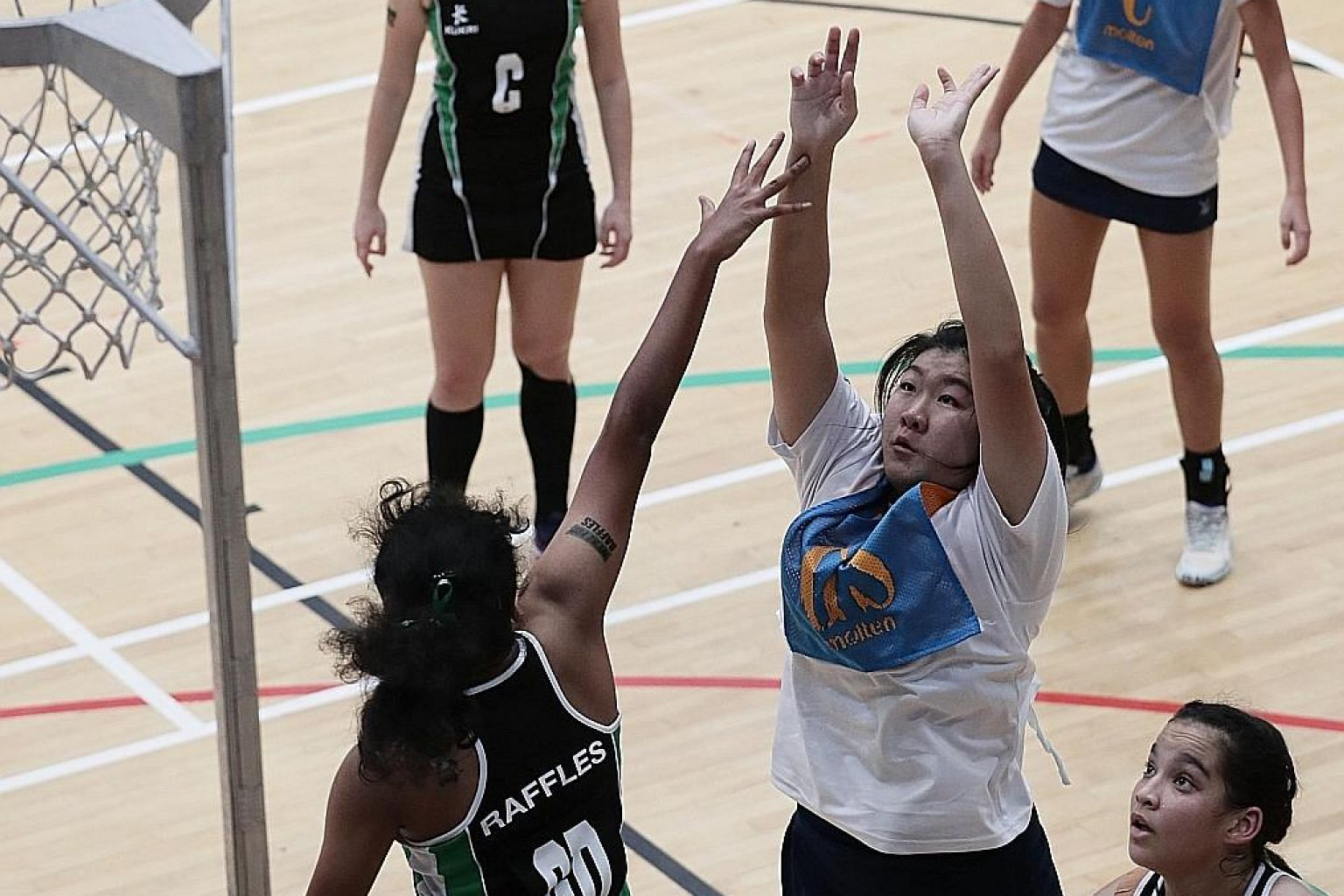 Anglo-Chinese Junior College's goal-shooter Syntyche Yeo taking a shot while guarded by Raffles Institution captain Keziah Vickraman in the A Division netball final at Jurong East Sports Hall yesterday. Syntyche scored 49 of her team's 53 points. ST