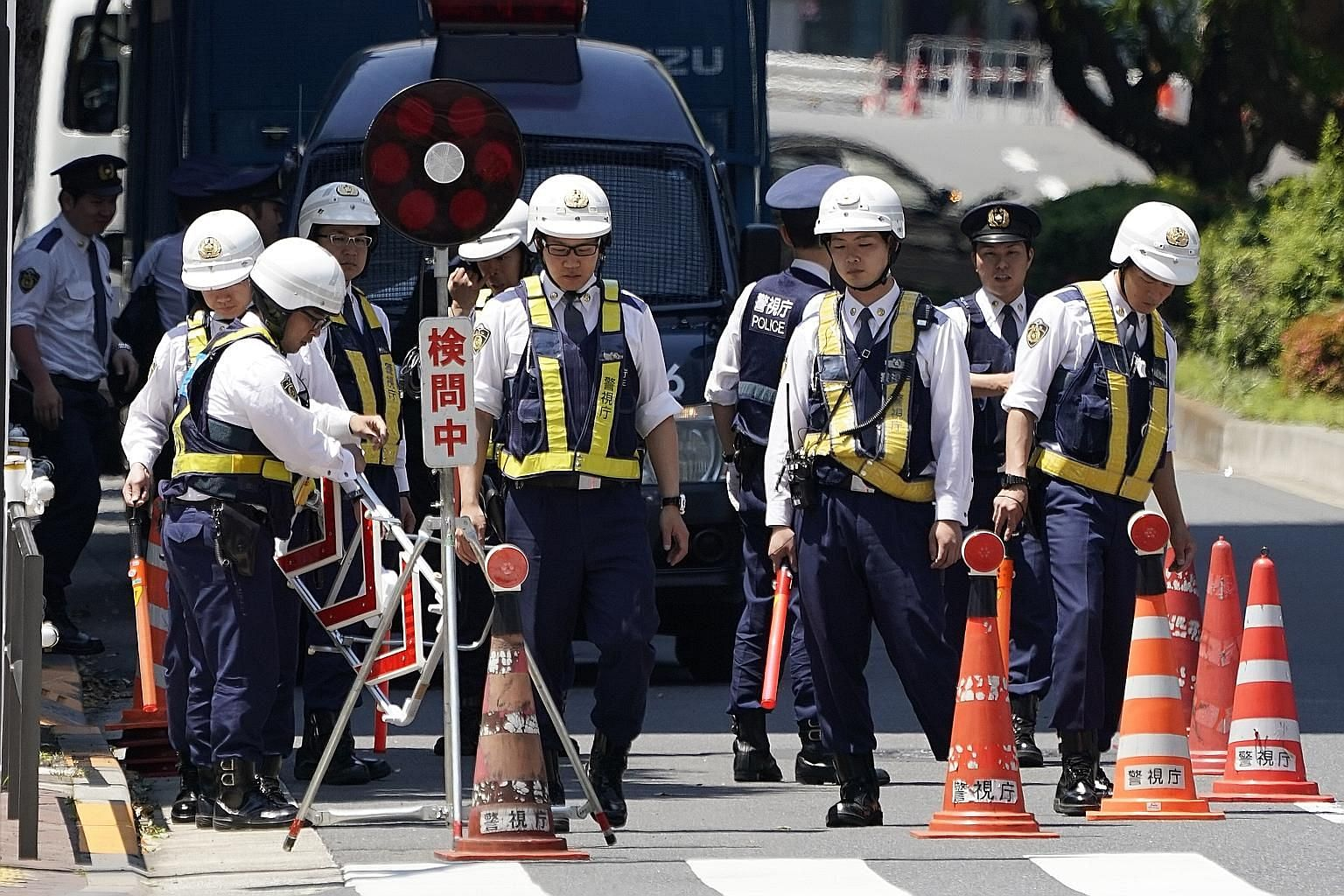 Police officers setting up barricades in front of the American embassy in Tokyo yesterday, ahead of US President Donald Trump's state visit to Japan today.