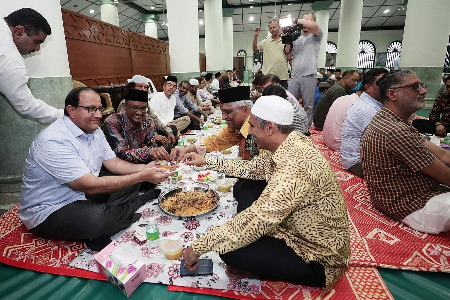 Minister for Communications and Information S. Iswaran (left) at an iftar, or break-fast session, at the Masjid Jamae Chulia in South Bridge Road yesterday. Community and business leaders, as well as people of different faiths, attended the event, co