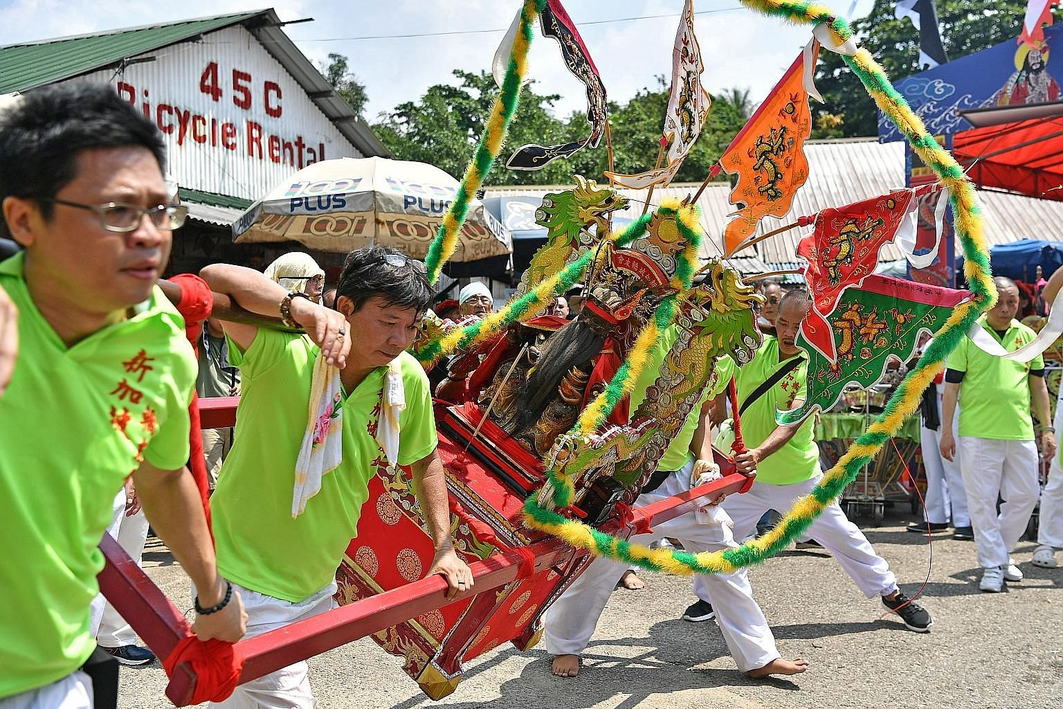 Above: A dragon dance troupe - one of five taking part in the celebrations - arriving at Ubin on May 12. Right: A pagoda-shaped incense furnace was rebuilt based on the original one. The new temple is also identical in design to the one it replaced.