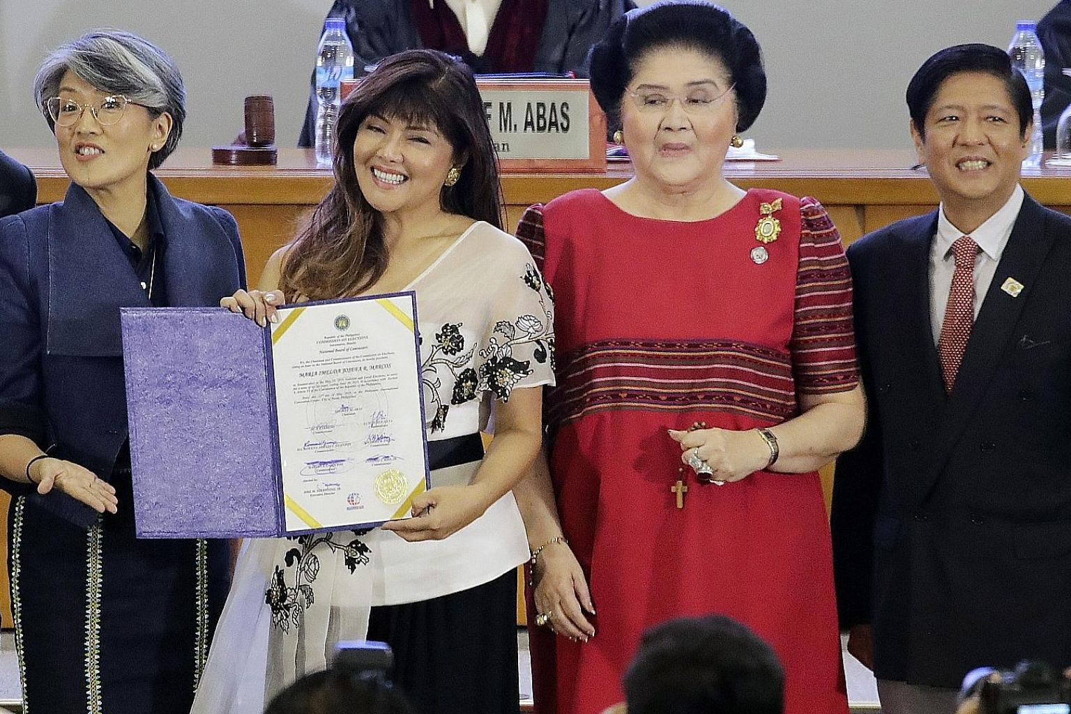Senator-elect Imee Marcos, daughter of former strongman Ferdinand Marcos, holding her certificate next to her mother Imelda Marcos (in red), brother Bongbong and sister Irene during a proclamation of senators-elect in Manila, on May 22. A sweep by Pr