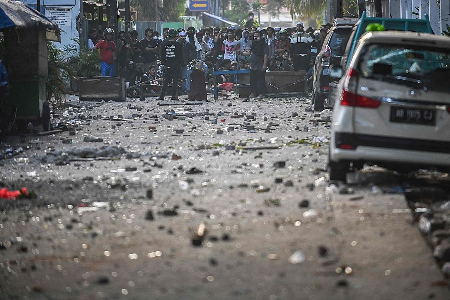 A mob seen in the background amid scattered rocks on the street during a violent overnight demonstration near the building housing the election supervisory agency Bawaslu in Jakarta last Wednesday. Riots in the capital claimed the lives of eight peop