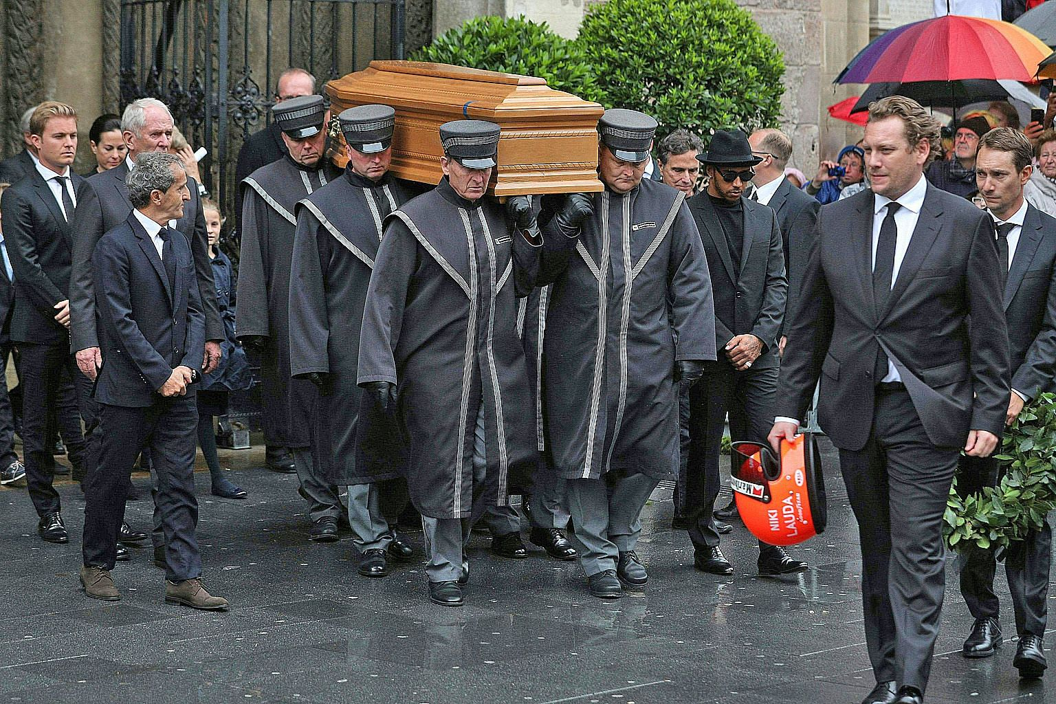 (From left) 2016 Formula One champion Nico Rosberg, four-time winner Alain Prost, Mercedes' defending champion Lewis Hamilton and Niki Lauda's sons Lukas and Mathias escorting the coffin of the late three-time world champion as it is being carried ou
